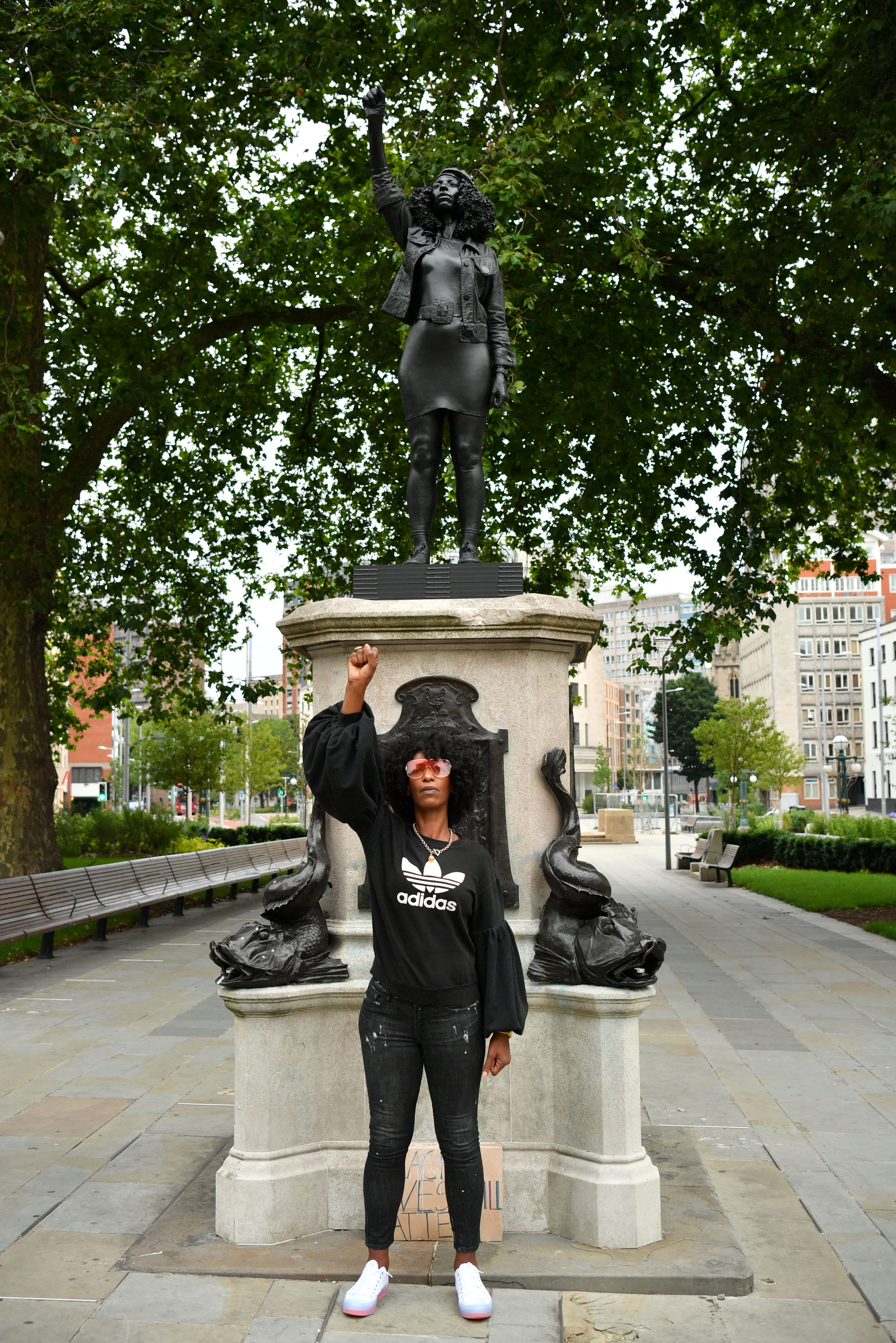 BRISTOL, ENGLAND - JULY 15: Black Lives Matter protestor Jen Reid poses for a photograph in front of a sculpture of herself, by local artist Marc Quinn, on the plinth where the Edward Colston statue used to stand on July 15, 2020 in Bristol, England. A statue of slave trader Edward Colston was pulled down and thrown into Bristol Harbour during Black Lives Matter protests sparked by the death of an African American man, George Floyd, while in the custody of Minneapolis police in the United States of America. The Mayor of Bristol has since announced the setting up of a commission of historians and academics to reassess Bristol's landmarks and buildings that feature the name of Colston and others who made fortunes in trades linked to slavery. (Photo by Matthew Horwood/Getty Images)