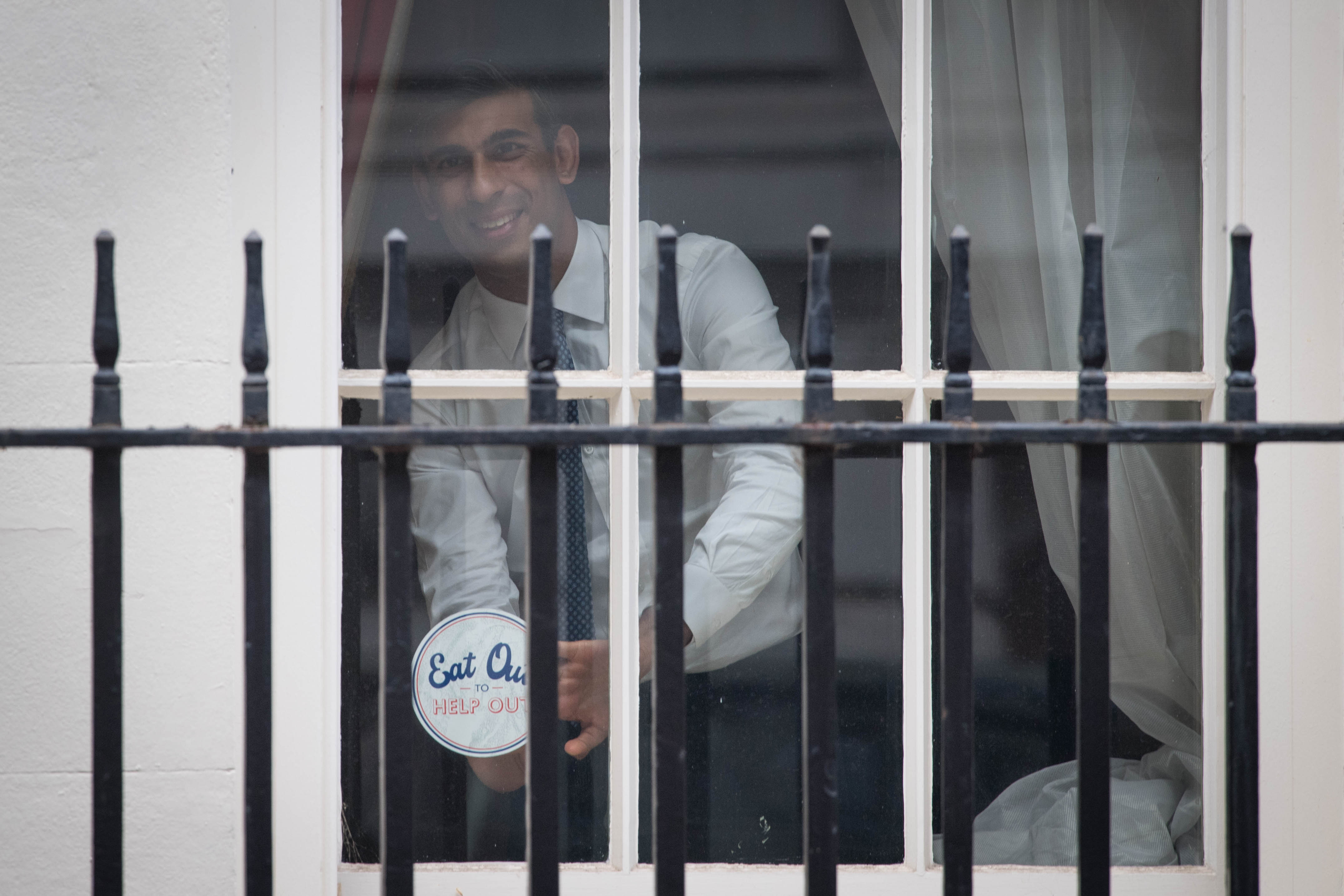 Chancellor Rishi Sunak places an 'Eat out to help out' sticker in the window of No.11 Downing Street in London, ahead of the new scheme encouraging customers to return to the hospitality industry. The initiative will provide up to £10 off meals to diners eating out every Monday, Tuesday and Wednesday during August at participating businesses across the UK. PA Photo. Picture date: Thursday July 16, 2020. See PA story HEALTH Coronavirus. Photo credit should read: Stefan Rousseau/PA Wire