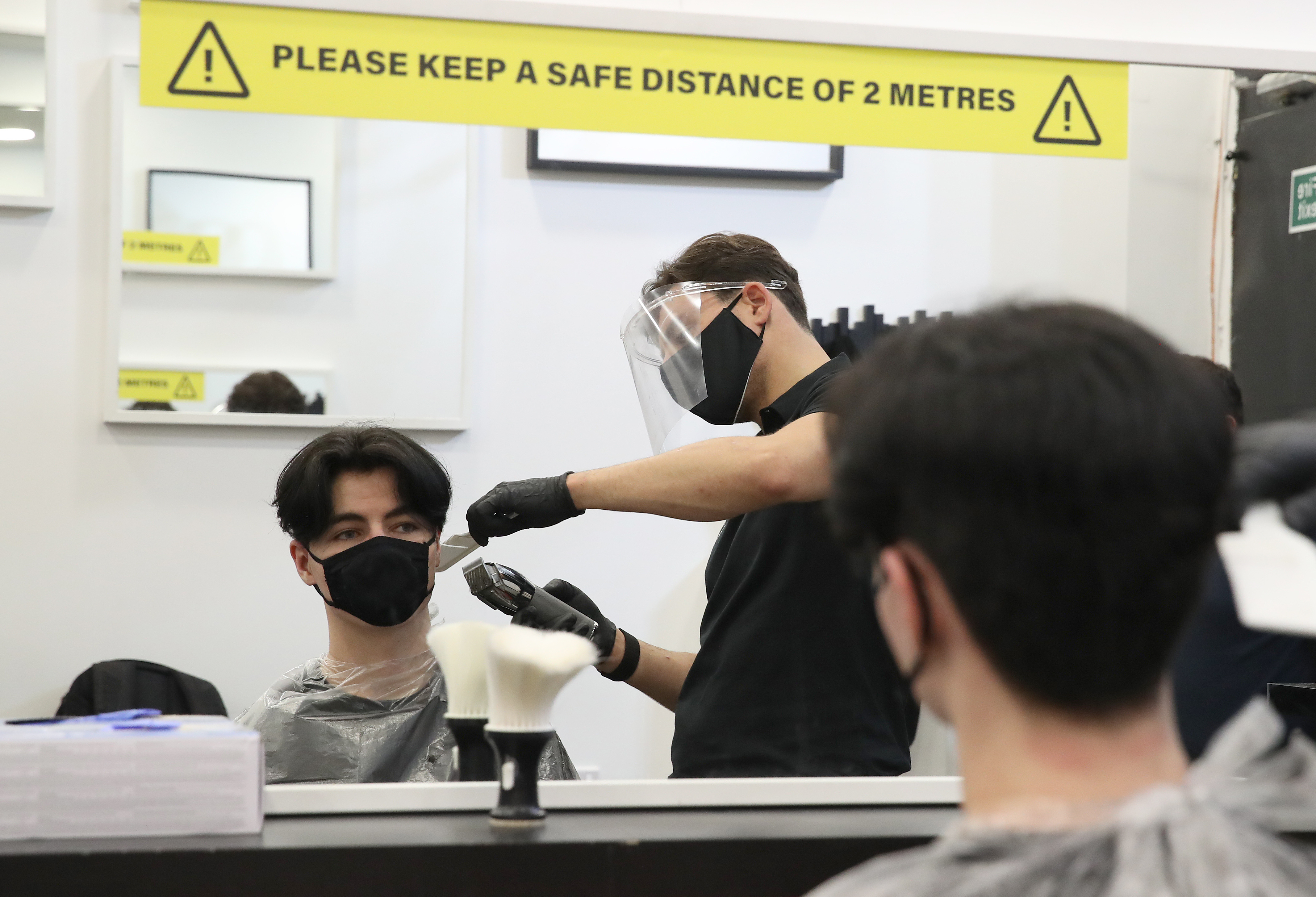 Barber Tony Mann with customer Sean Munro in the chair at Tony Mann's Barber Shop in Giffnock, Glasgow which opened at midnight as lockdown restrictions are relaxed. (Photo by Andrew Milligan/PA Images via Getty Images)