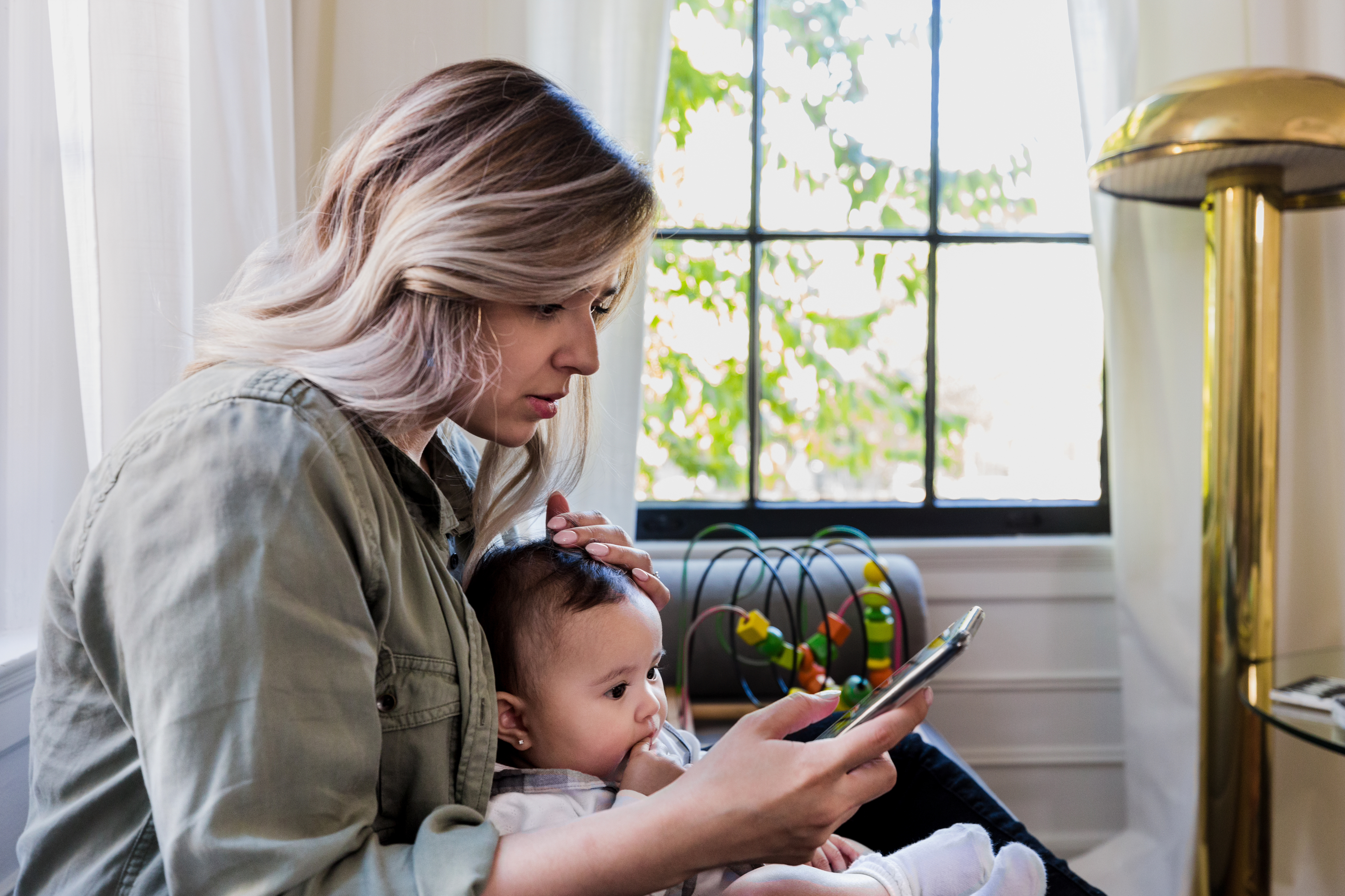The worried mid adult mother uses her smart phone to find information about illness in babies.