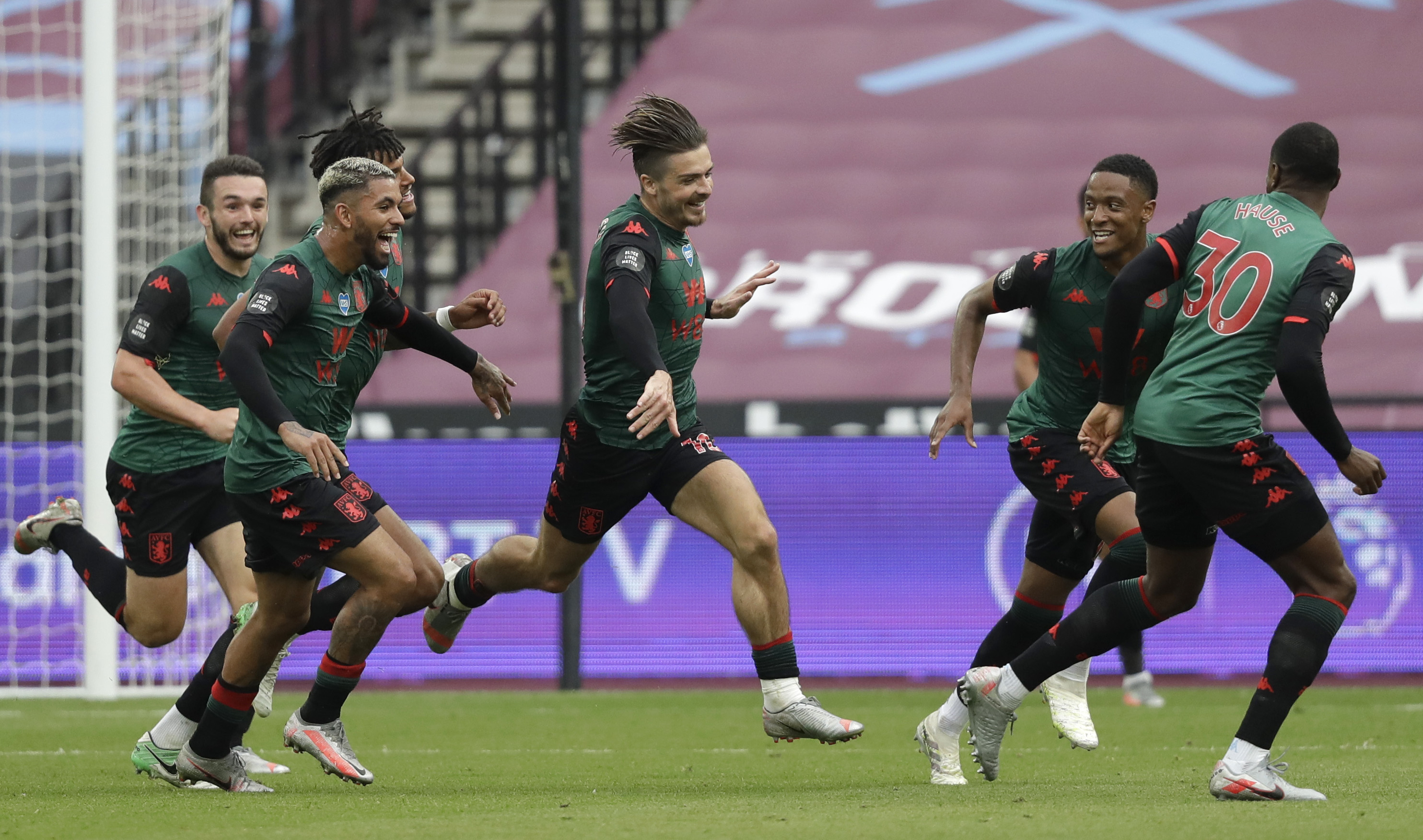 Aston Villa's Jack Grealish, centre,celebrates with teammates after scoring the opening goal of the game during the English Premier League soccer match between West Ham United and Aston Villa at the London Stadium in London, Sunday, July 26, 2020. (AP Photo/Matt Dunham)