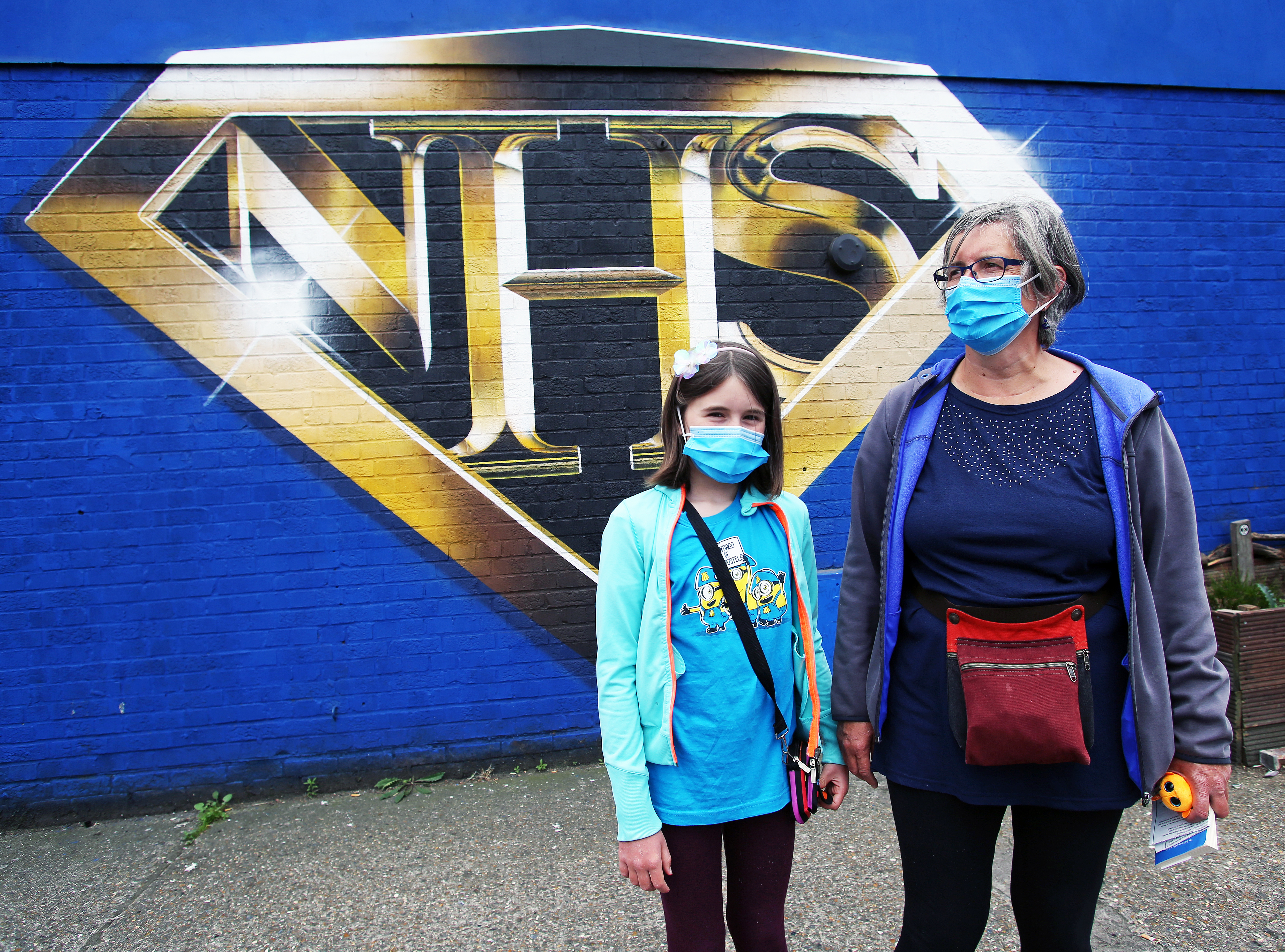 An NHS worker and her daughter, who both wear protective masks, stand in front of an NHS superman graffiti that pays tribute to NHS workers on a wall in Tulse Hill, London, as the UK continues to recover from the coronavirus pandemic.