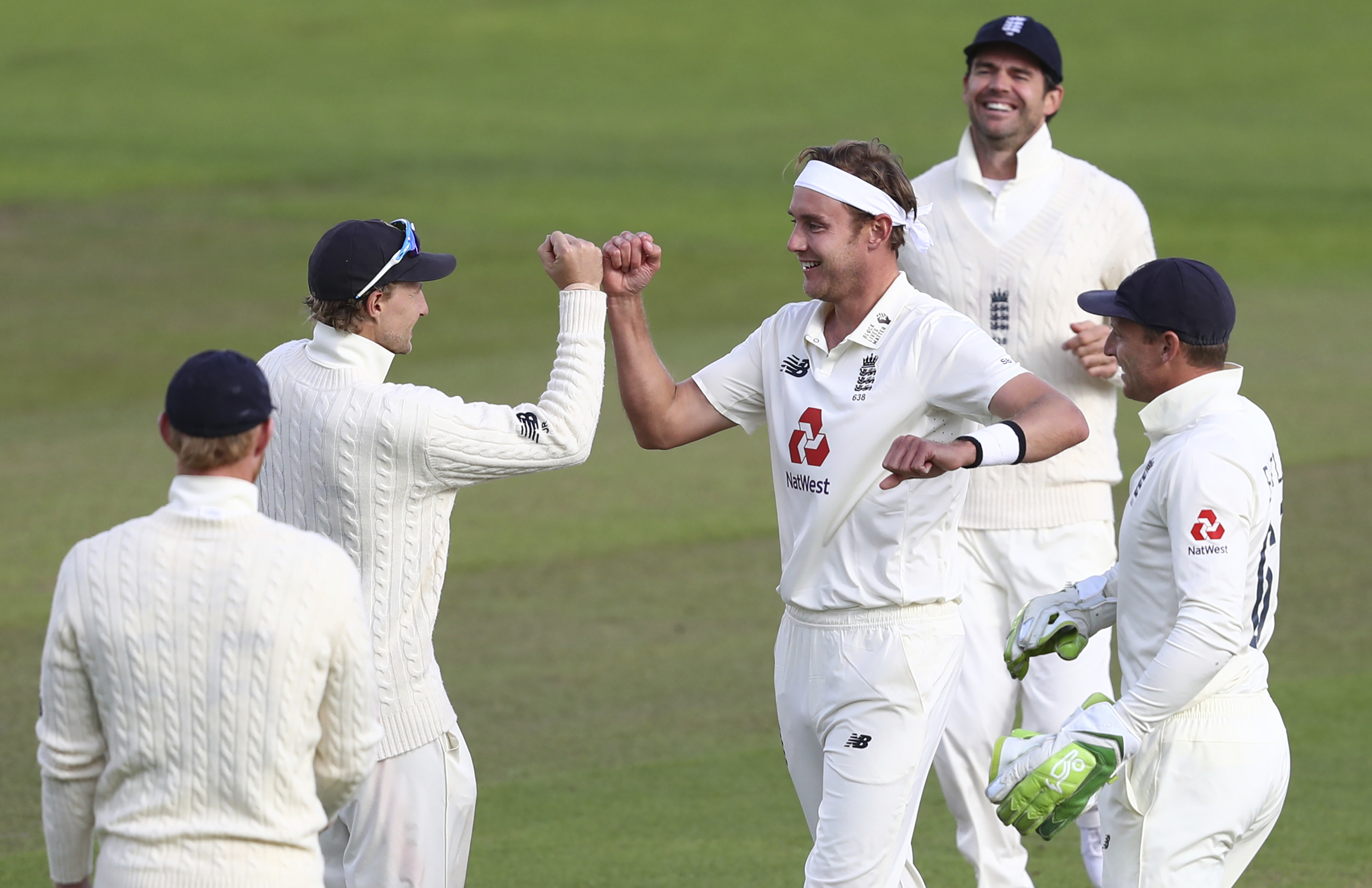 England's Stuart Broad, center, celebrates with teammates the dismissal of West Indies' John Campbell during the third day of the third cricket Test match between England and West Indies at Old Trafford in Manchester, England, Sunday, July 26, 2020. (Michael Steele/Pool via AP)