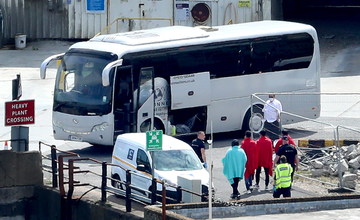 Border Force officers escort men thought to be migrants to a waiting bus in Dover, Kent, after small boat incidents in The Channel earlier this morning. Home Secretary, Priti Patel, is set to unveil details of how the UK's points-based immigration system - which will come into effect on January 1 after freedom of movement ends - will operate.