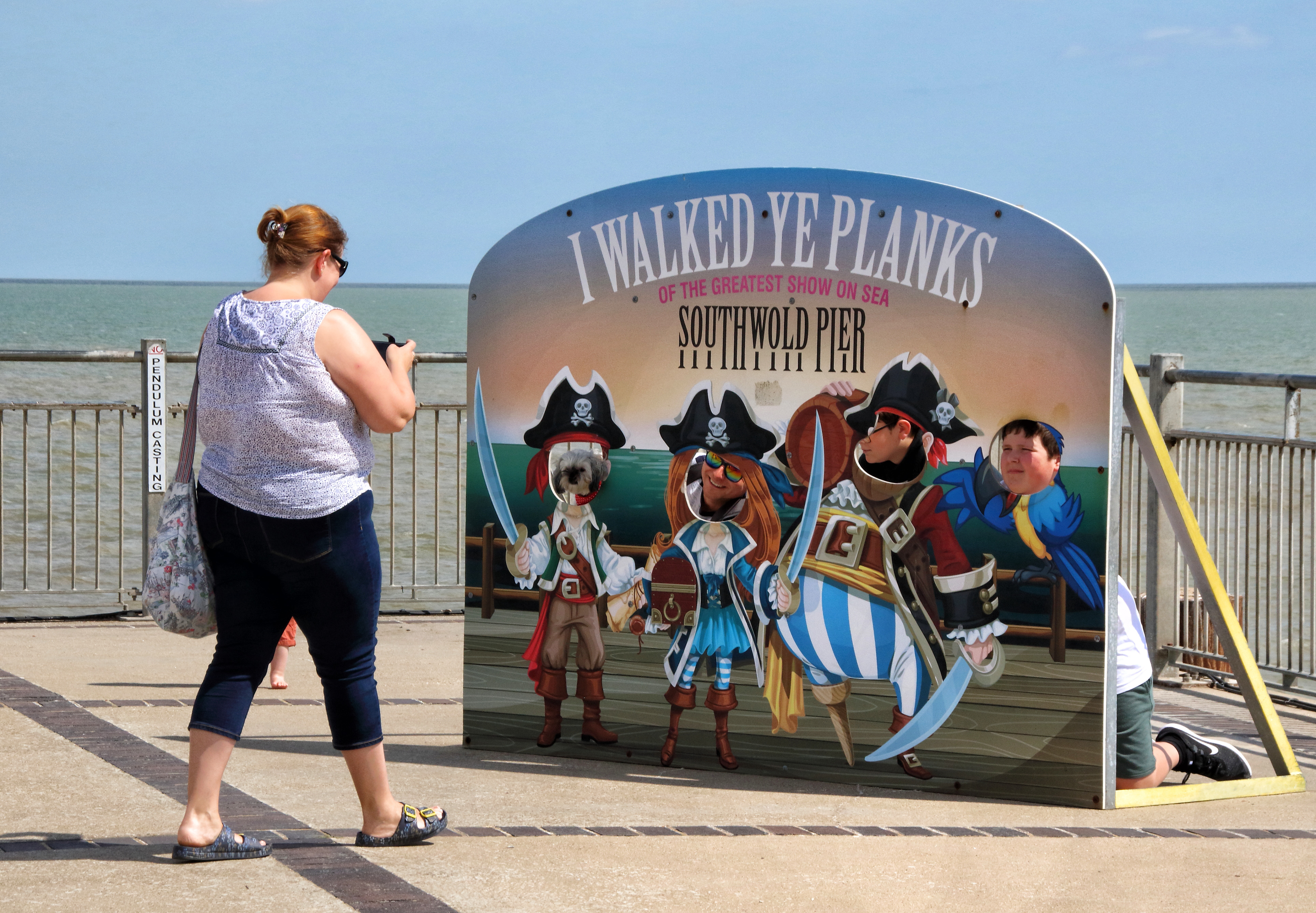 A woman takes a photo of 'I walked ye planks' fun pirate pop up on the Pier. With the beaches in England now fully opened with only social distancing measures in force, people are taking the chance to visit some coastal resorts. Southwold is an English resort town full of an olde world charm and famous for its 300 brightly coloured beach huts. Plenty of people were out and about on the sandy beach and on the pier. (Photo by Keith Mayhew / SOPA Images/Sipa USA)