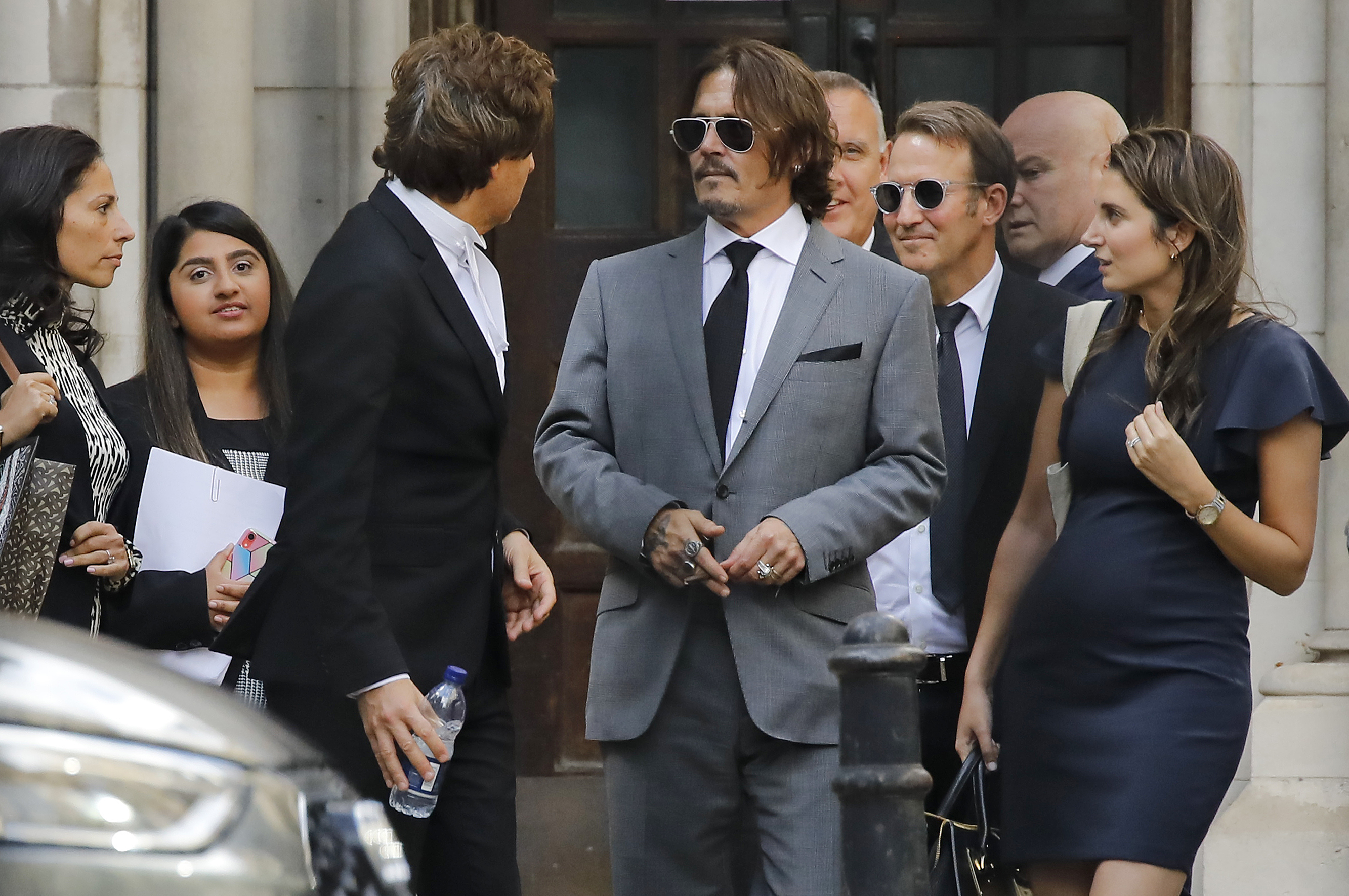 """US actor Johnny Depp (C) leaves after the fifth day of his libel trial against News Group Newspapers (NGN), at the High Court in London, on July 13, 2020. - Depp is suing the publishers of The Sun and the author of the article for the claims that called him a """"wife-beater"""" in April 2018. (Photo by Tolga AKMEN / AFP) (Photo by TOLGA AKMEN/AFP via Getty Images)"""