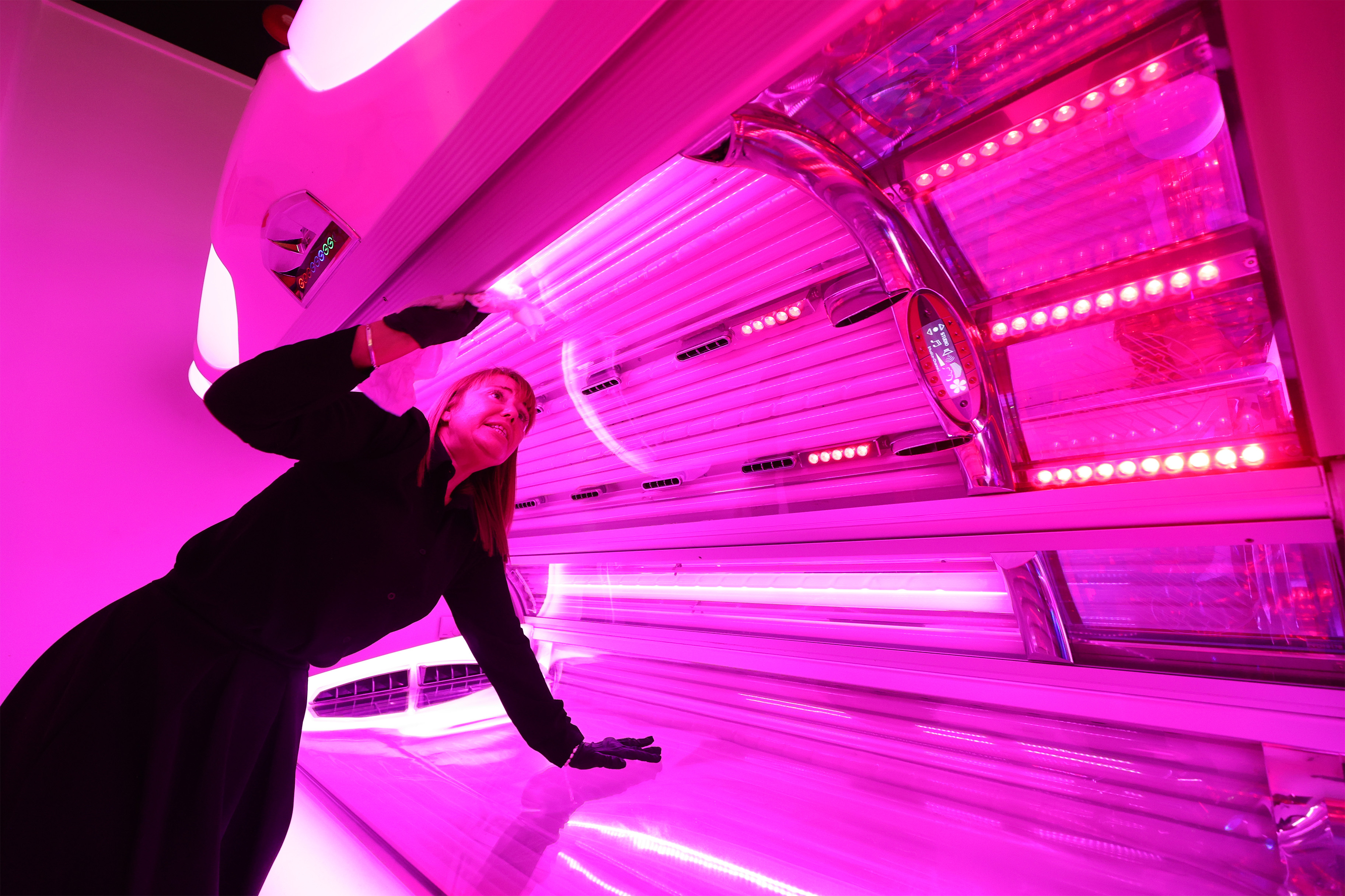 Manager of the store Kerry-Anne Walker sanitises a sunbed at The Tanning Shop on the Isle of Dogs, east London, as they reopen to customers following the easing of lockdown restrictions in England (Photo by Yui Mok/PA Images via Getty Images)