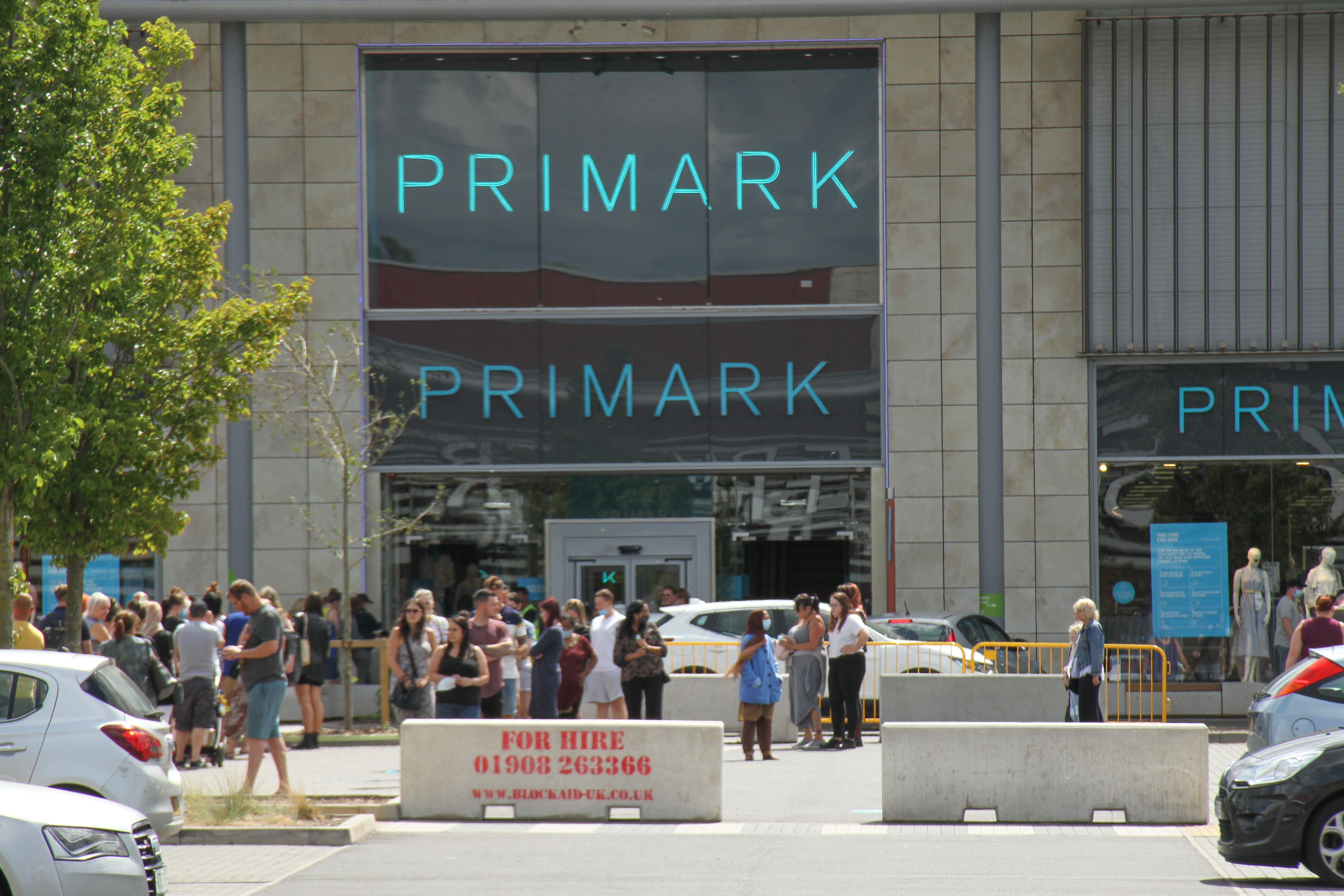 Customers queue outside the Primark store in Rushden Lakes. The Government has made it mandatory to wear face coverings in all public transport, supermarkets and indoor shopping centers as a measure to combat the spread of the novel coronavirus. (Photo by David Mbiyu / SOPA Images/Sipa USA)