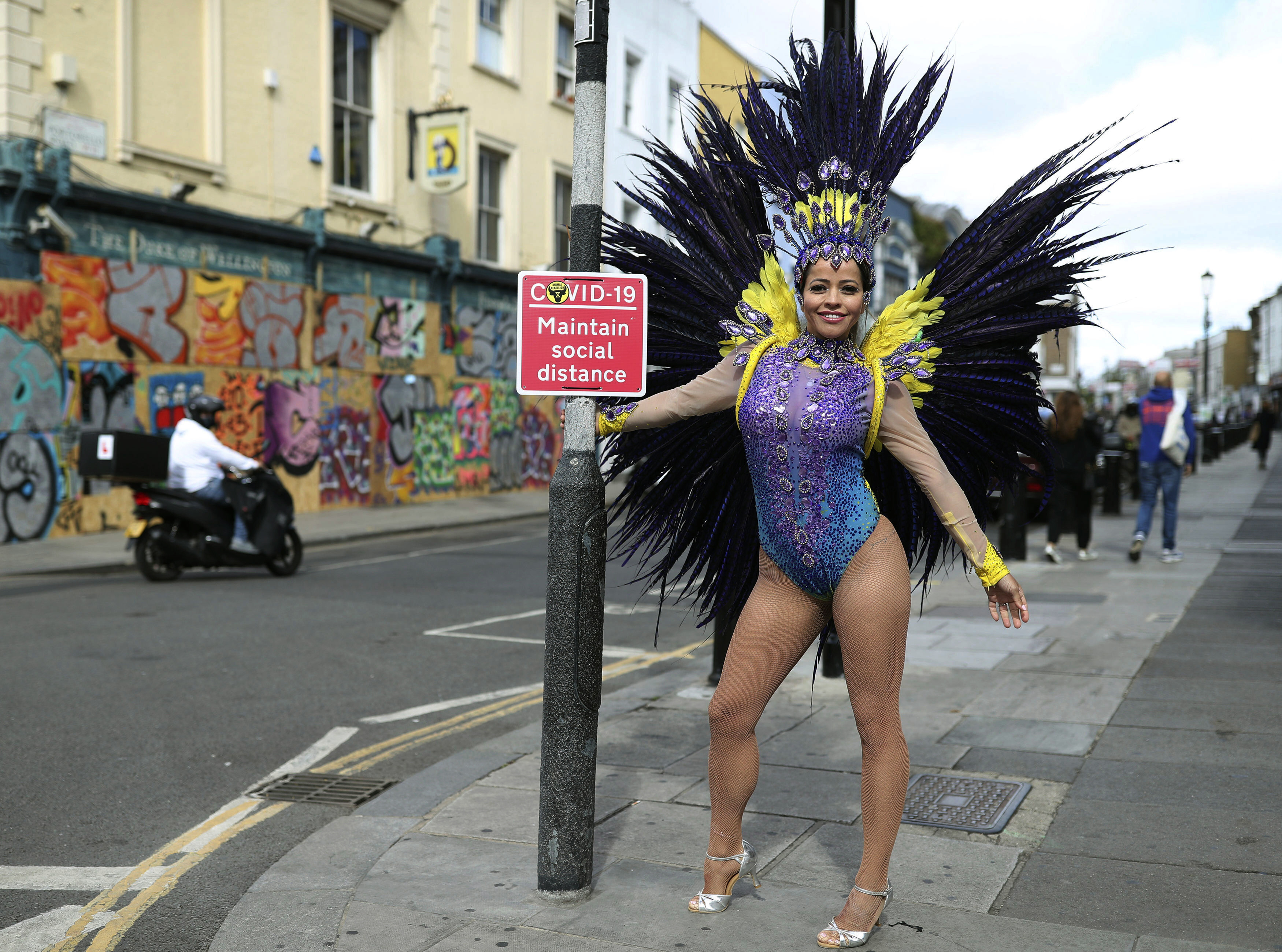 Pilates instructor Juliana Campos poses in her carnival costume in Notting Hill, London, on what would have been the weekend of the Notting Hill Carnival, after the 2020 carnival was cancelled due to the coronavirus pandemic, Sunday, Aug. 30, 2020. (Yui Mok/PA via AP)