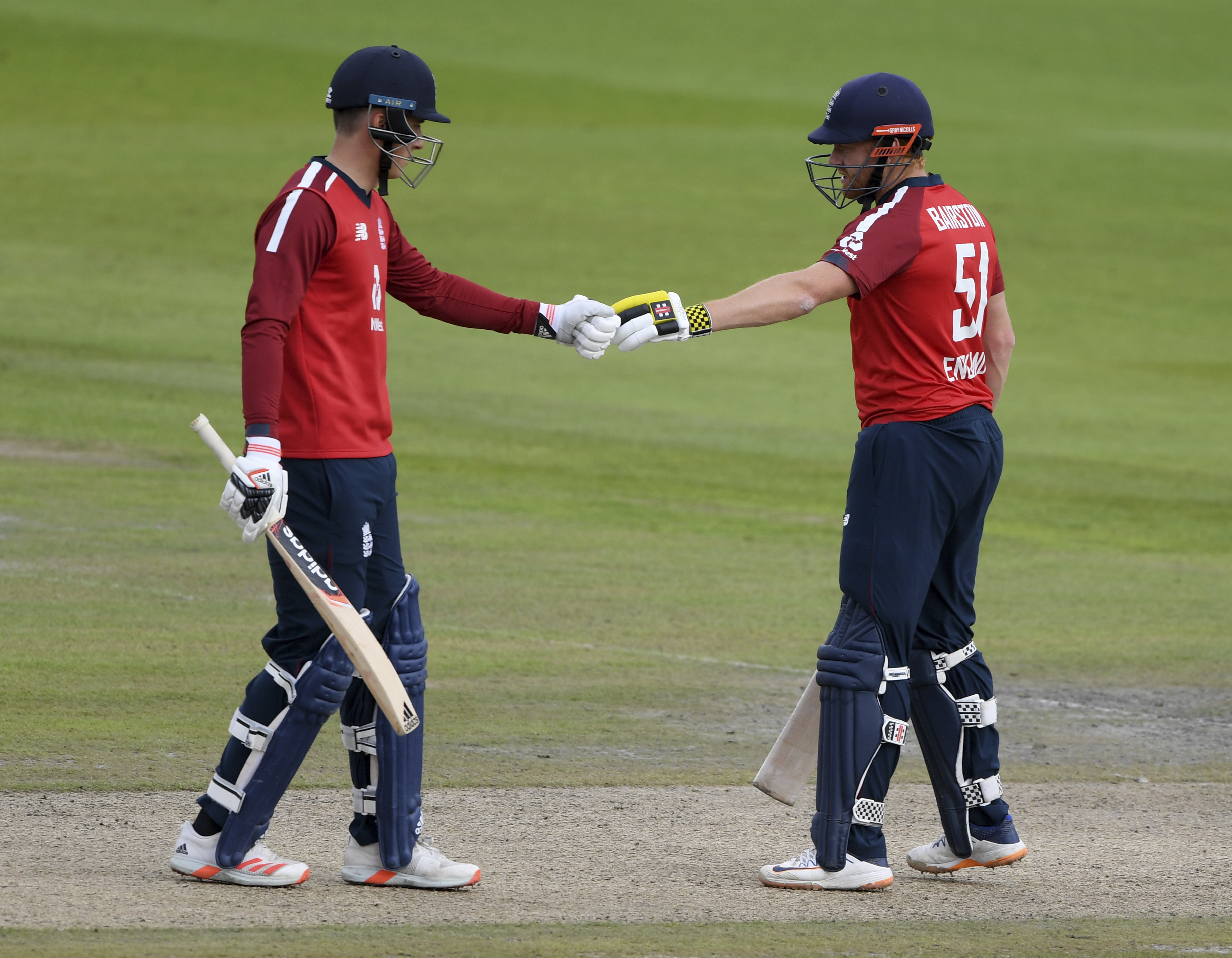England's Tom Banton, left, fist bumps with batting partner Jonny Bairstow during the second Twenty20 cricket match between England and Pakistan, at Old Trafford in Manchester, England, Sunday, Aug. 30, 2020. (Mike Hewitt/Pool via AP)