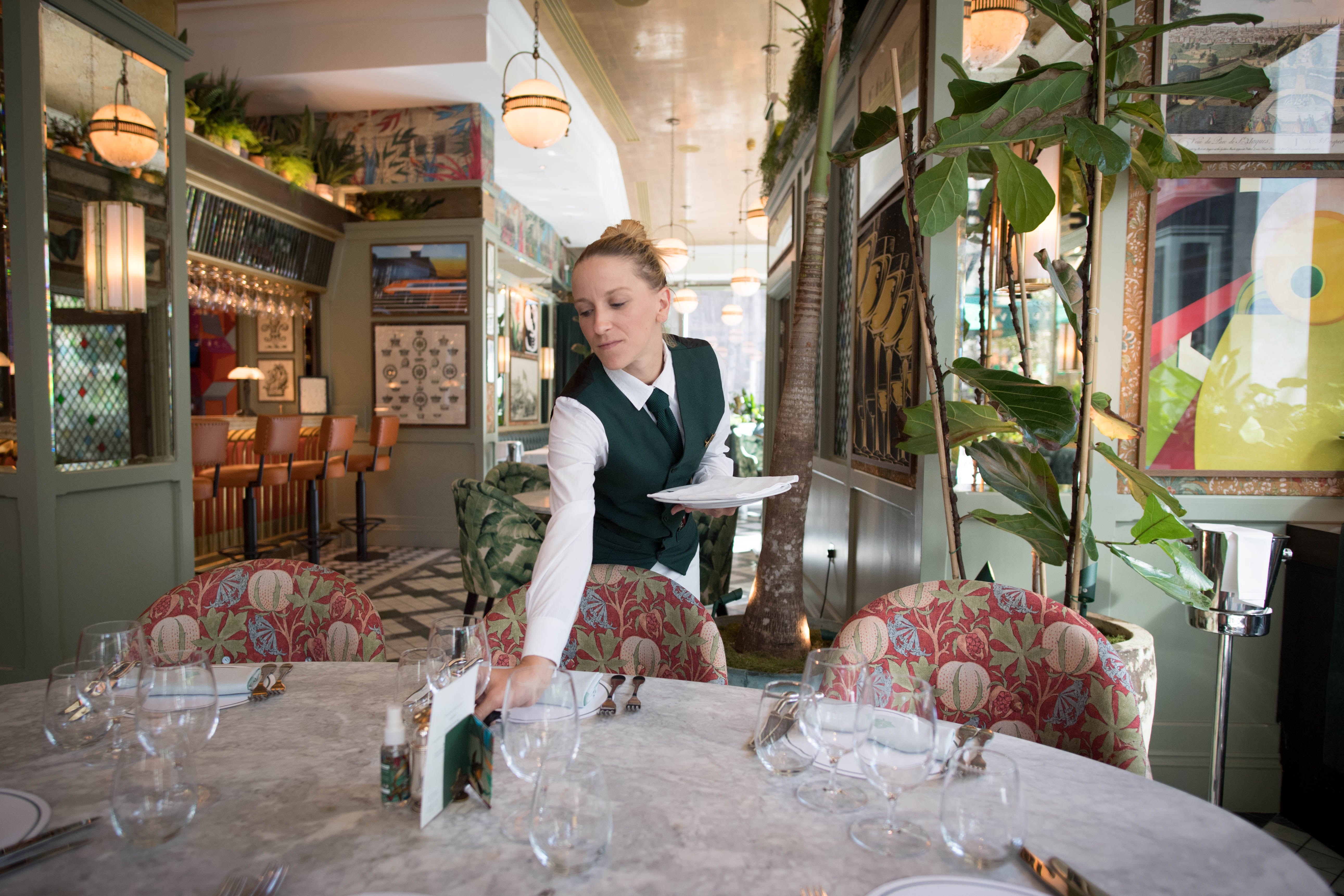 Staff at the Ivy Victoria in London, prepare the dining area, as the government initiative Eat Out to Help Out comes to an end. (Photo by Stefan Rousseau/PA Images via Getty Images)