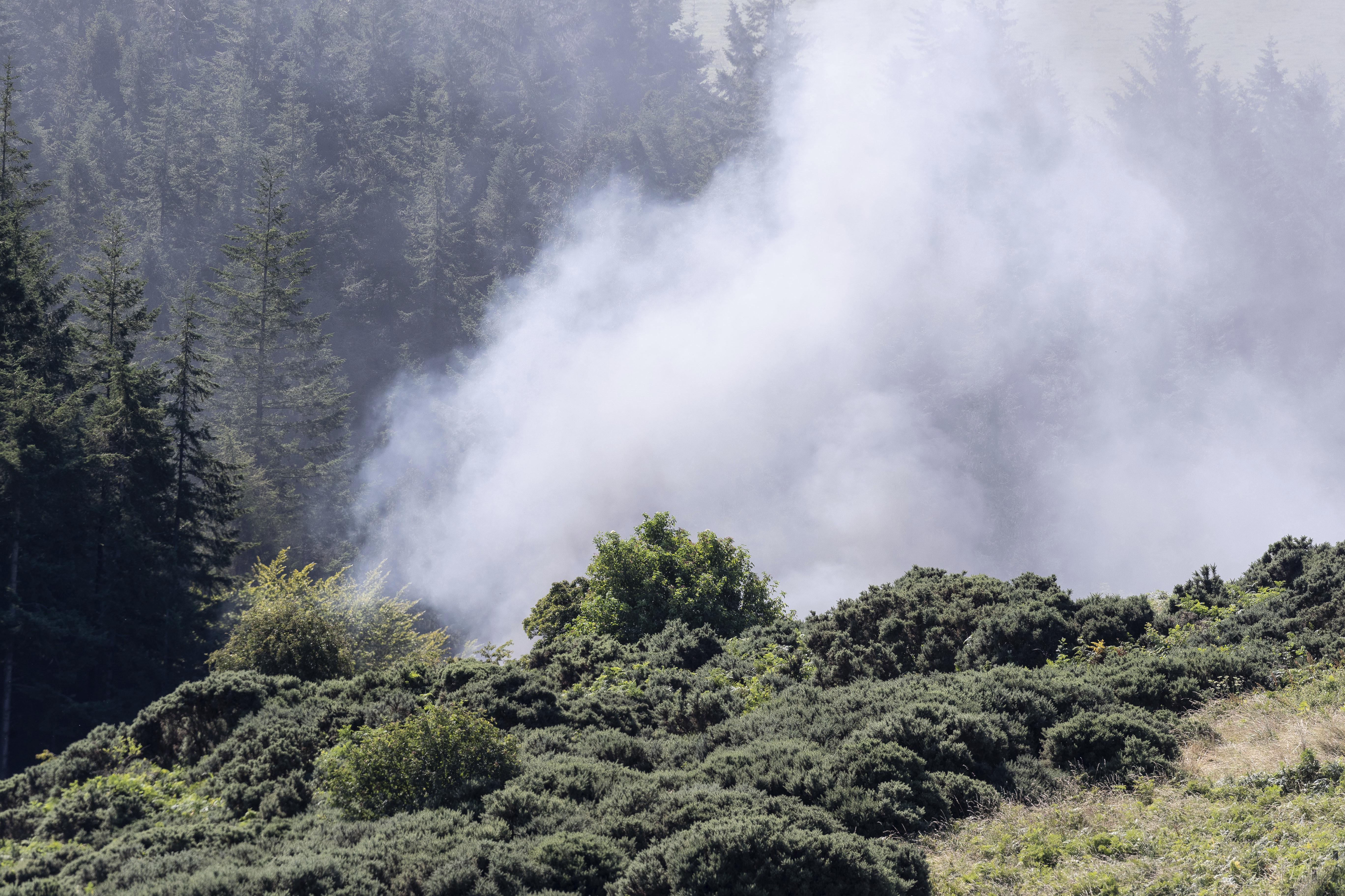 Smoke billows from the scene of a derailed train in Stonehaven, Scotland, Wednesday Aug. 12, 2020. Police and paramedics were responding Wednesday to a train derailment in northeast Scotland, where smoke could be seen rising from the site. Officials said there were reports of serious injuries. The hilly area was hit by storms and flash flooding overnight. (Derek Ironside/Newsline-media via AP)