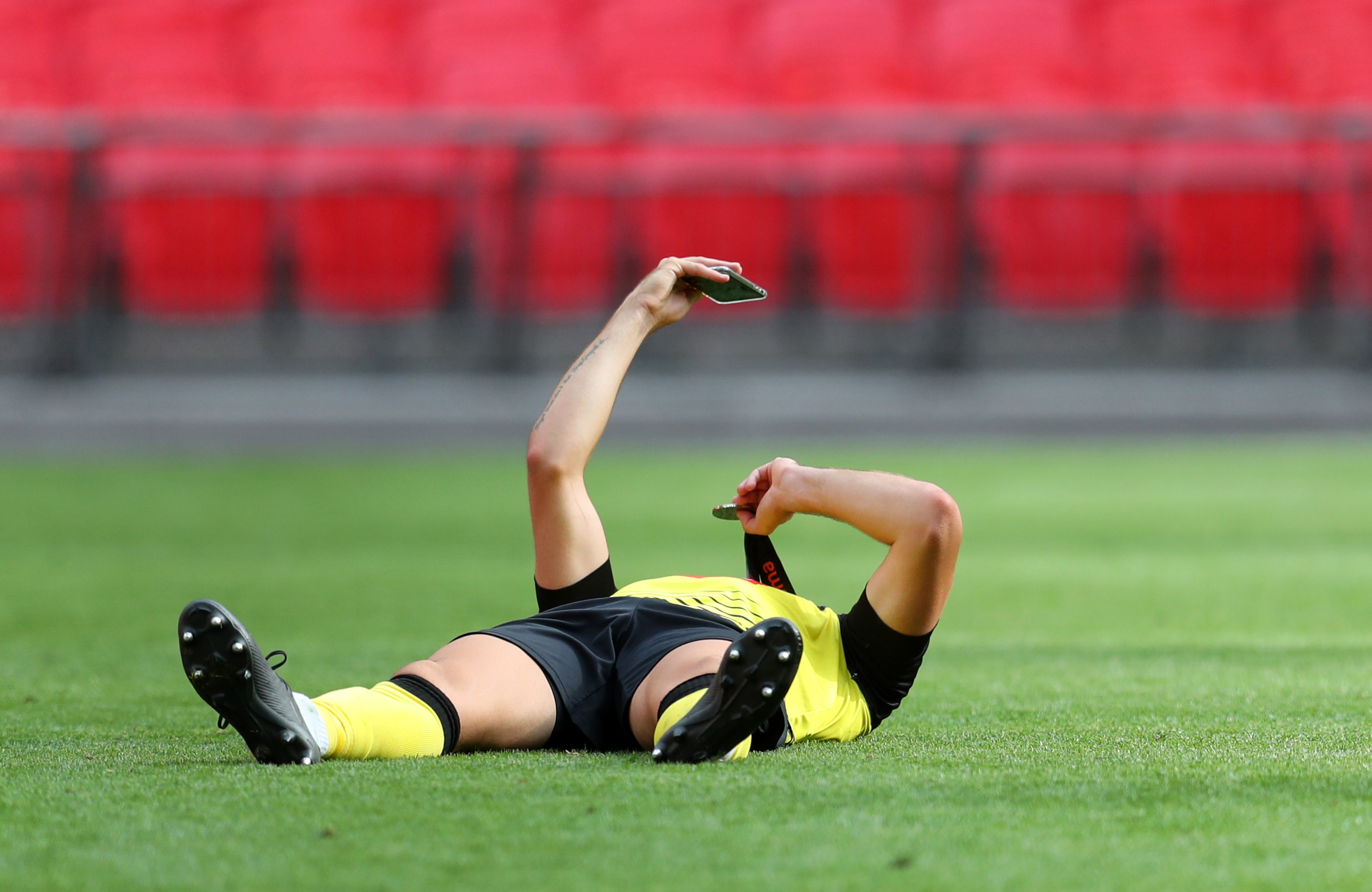 LONDON, ENGLAND - AUGUST 02: A Harrogate Town player holds up his medal as he talks to someone on his phones following the Vanarama National League Play Off Final match between Harrogate Town and Notts County  at Wembley Stadium on August 02, 2020 in London, England. (Photo by Catherine Ivill/Getty Images)