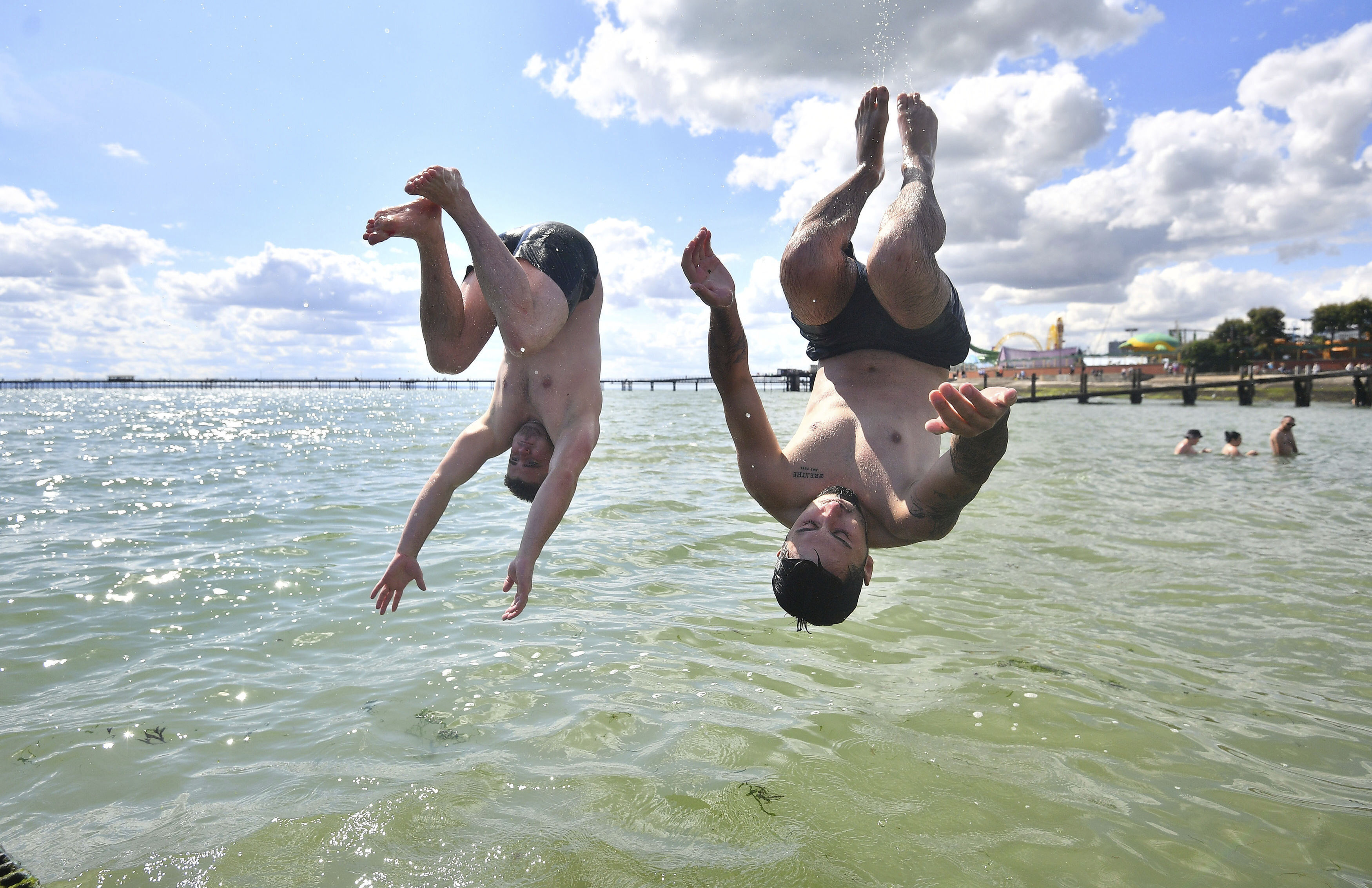 Men jump from a jetty into the water as the hot weather continues, at Southend-on-Sea, in England, Sunday, Aug. 2, 2020. (Victoria Jones/PA via AP)