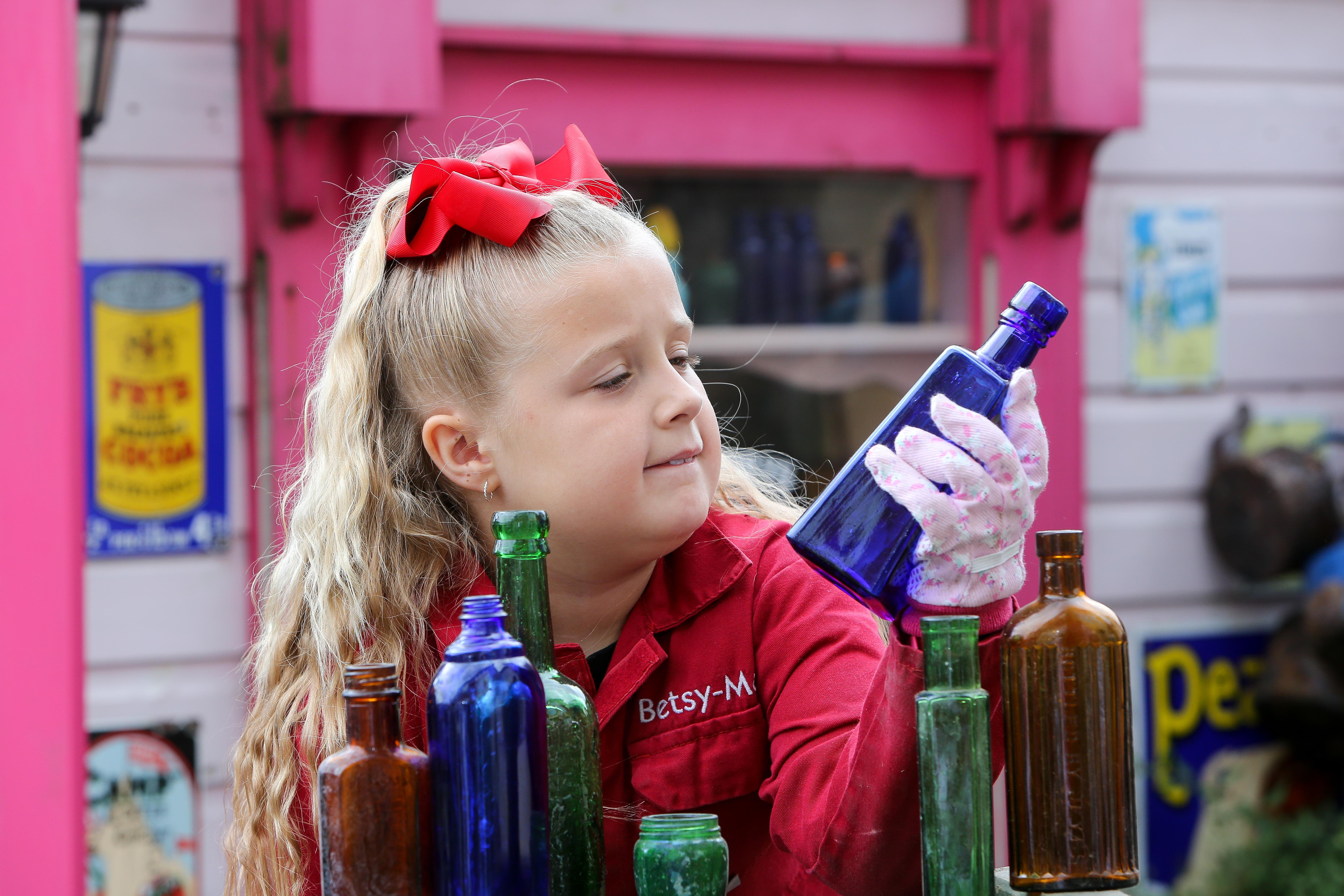 A seven-year-old schoolgirl is raking in hundreds of pounds by selling antique bottles from a little shop in her back garden - after digging them up from old landfill sites. Betsy-Mae Lloyd has been coining it in after launching her own business at her parents' home while still attending primary school.  The young entrepreneur flogs old bottles, jars and teapots - dating back to between the 1870s and 1930 - which she finds on historic landfill sites in the West Midlands.  After taking them home and cleaning them up herself, she then stores them in a Victorian-style play shed, built by dad Jason, before listing them for sale on Facebook.