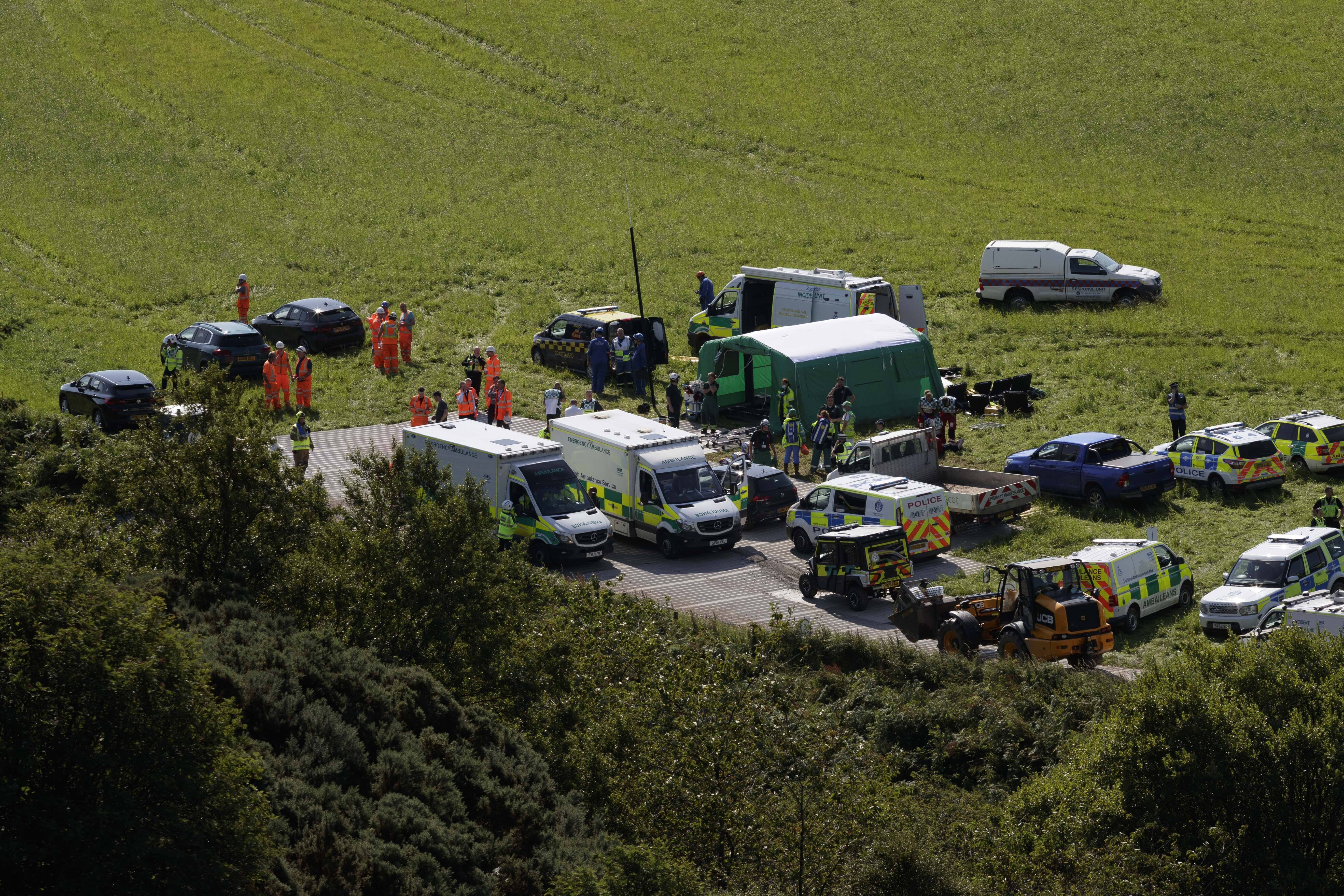 Emergency services attend the scene of a derailed train in Stonehaven, Scotland, Wednesday Aug. 12, 2020. Police and paramedics were responding Wednesday to a train derailment in northeast Scotland, where smoke could be seen rising from the site. Officials said there were reports of serious injuries. The hilly area was hit by storms and flash flooding overnight. (Ross Johnston/Newsline-media via AP)