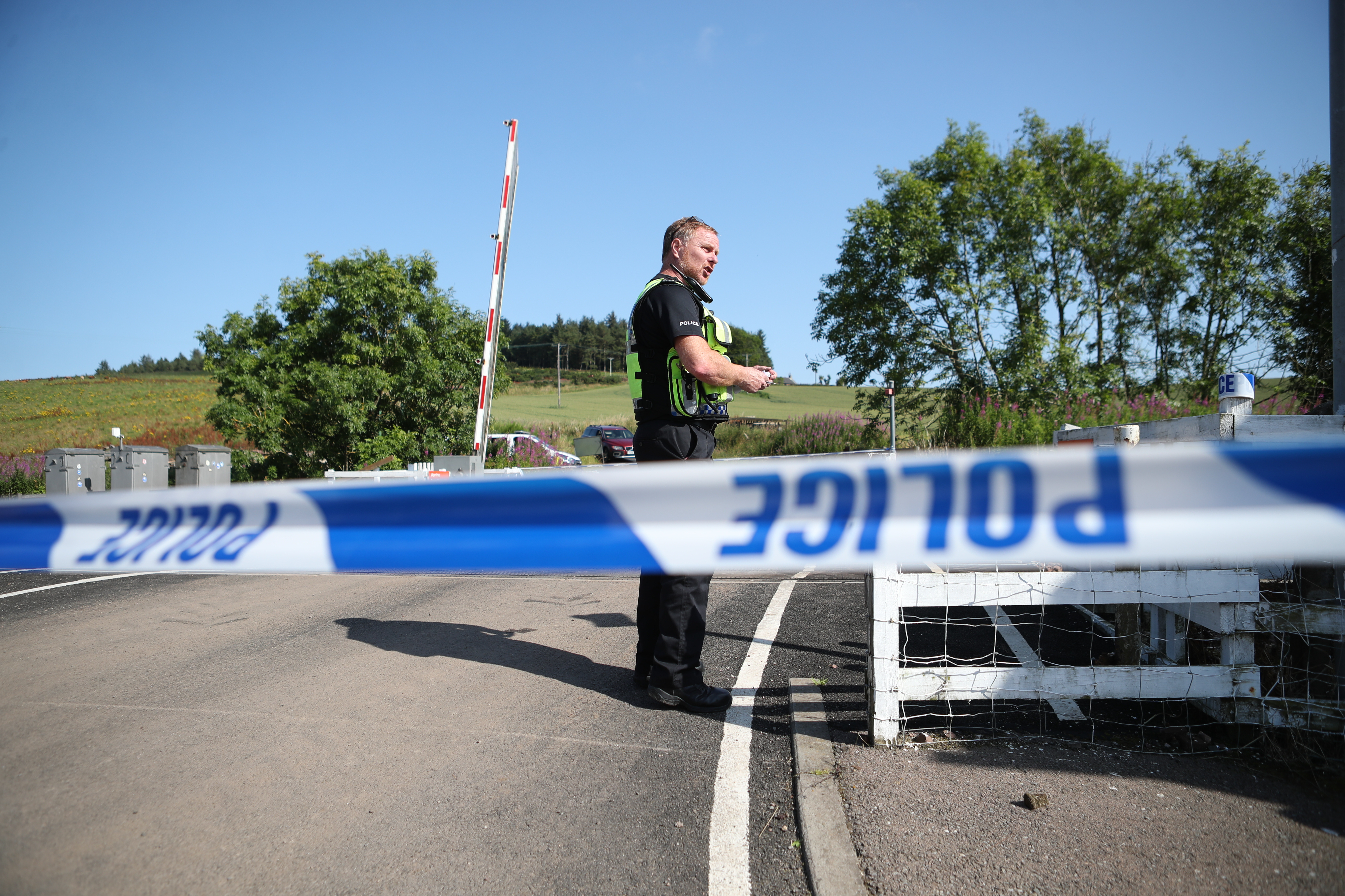 A police officer at a cordon at Carmont crossing, south of the scene in Stonehaven, Aberdeenshire, where the 06.38 Aberdeen to Stonehaven ScotRail train derailed at about 9.40am this morning. The fire service, police and ambulance service are in attendance and the incident is ongoing. (Photo by Jane Barlow/PA Images via Getty Images)