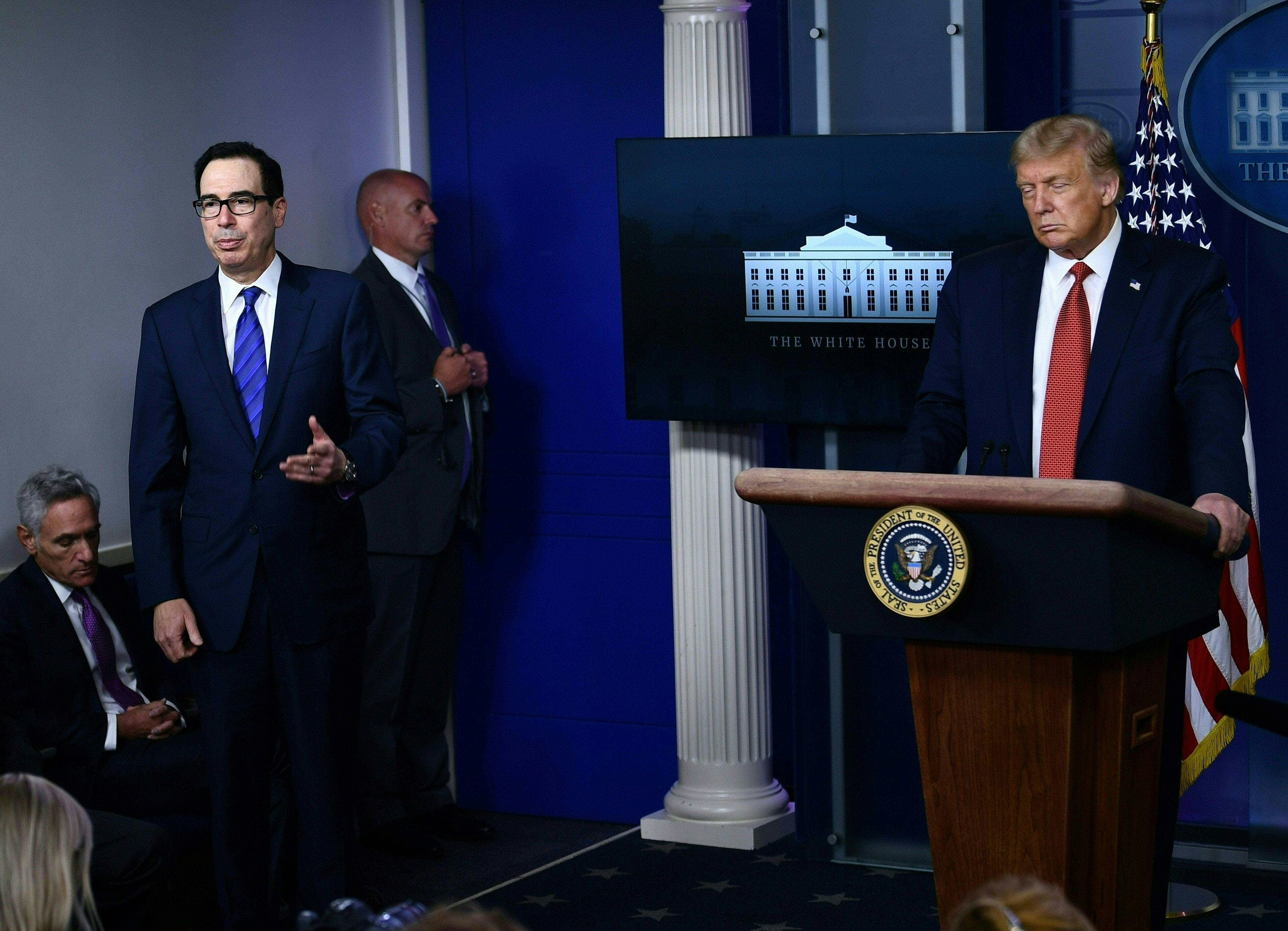 """US President Donald Trump listens to Treasury Secretary Steven Mnuchin in the Brady Briefing Room of the White House in Washington, DC, on August 10, 2020. - Secret Service guards shot a person, who was apparently armed, outside the White House on Monday, President Donald Trump said just after being briefly evacuated in the middle of a press conference. The president was abruptly ushered out of the press event and black-clad secret service agents with automatic rifles rushed across the lawn north of the White House. Minutes later, Trump reappeared at the press conference, where journalists had been locked in, and announced that someone had been shot outside the White House grounds. Trump said he knew nothing about the identity or motives of the person shot, but when asked if the person had been armed, answered: """"From what I understand, the answer is yes."""" (Photo by Brendan Smialowski / AFP) (Photo by BRENDAN SMIALOWSKI/AFP via Getty Images)"""