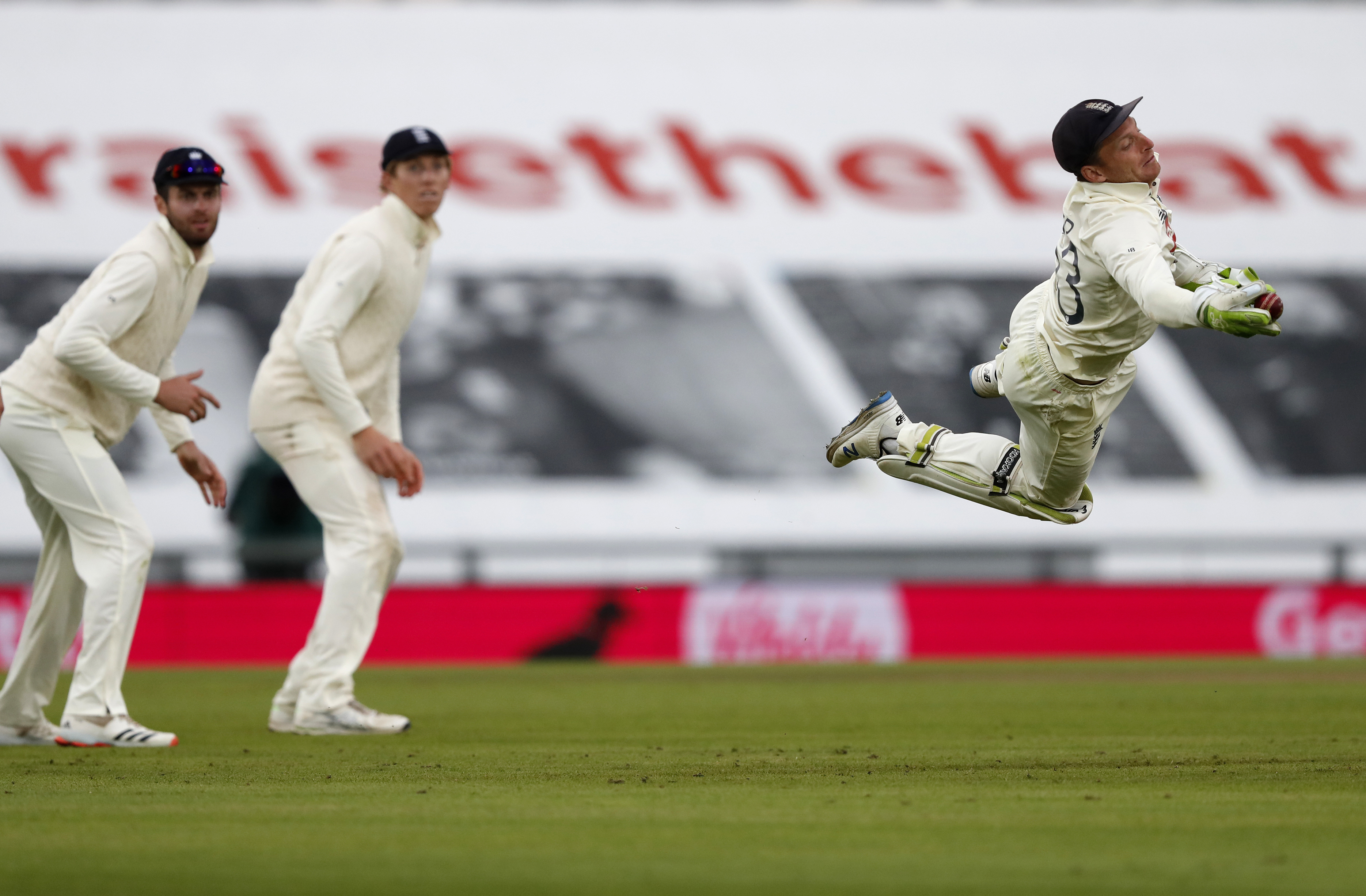 England's wicketkeeper Jos Buttler, right, dives to take the catch to dismiss Pakistan's Shaheen Afridi during the third day of the third cricket Test match between England and Pakistan, at the Ageas Bowl in Southampton, England, Sunday, Aug. 23, 2020. (AP Photo/Alastair Grant, Pool)