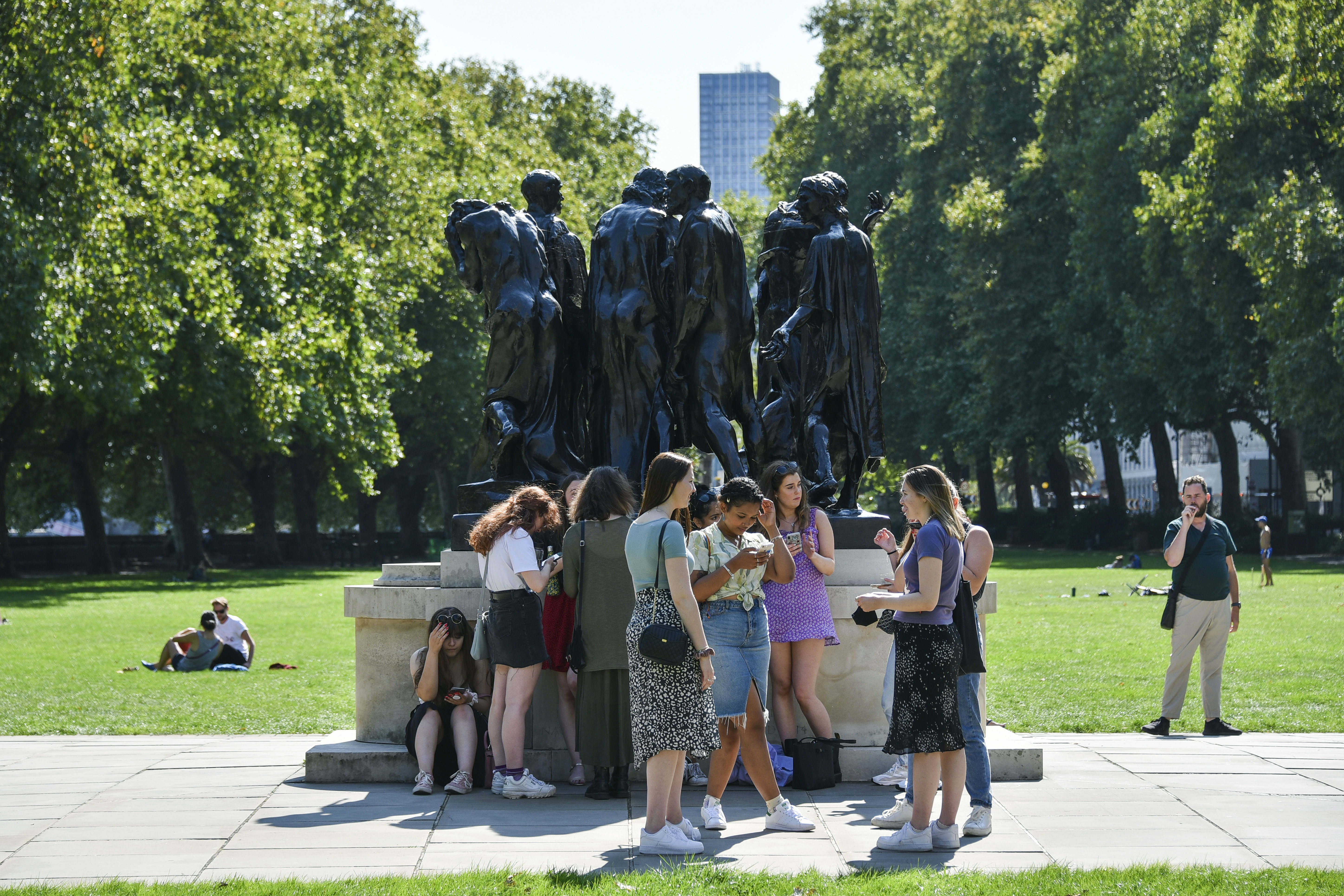 A group of people walk in Victoria Gardens, in London, Sunday, Sept. 13, 2020. From Monday, social gatherings of more than six people will be banned in England — both indoors and outdoors — and Boris Johnson hinted that such restrictions will potentially remain in place until or through Christmas. (AP Photo/Alberto Pezzali)