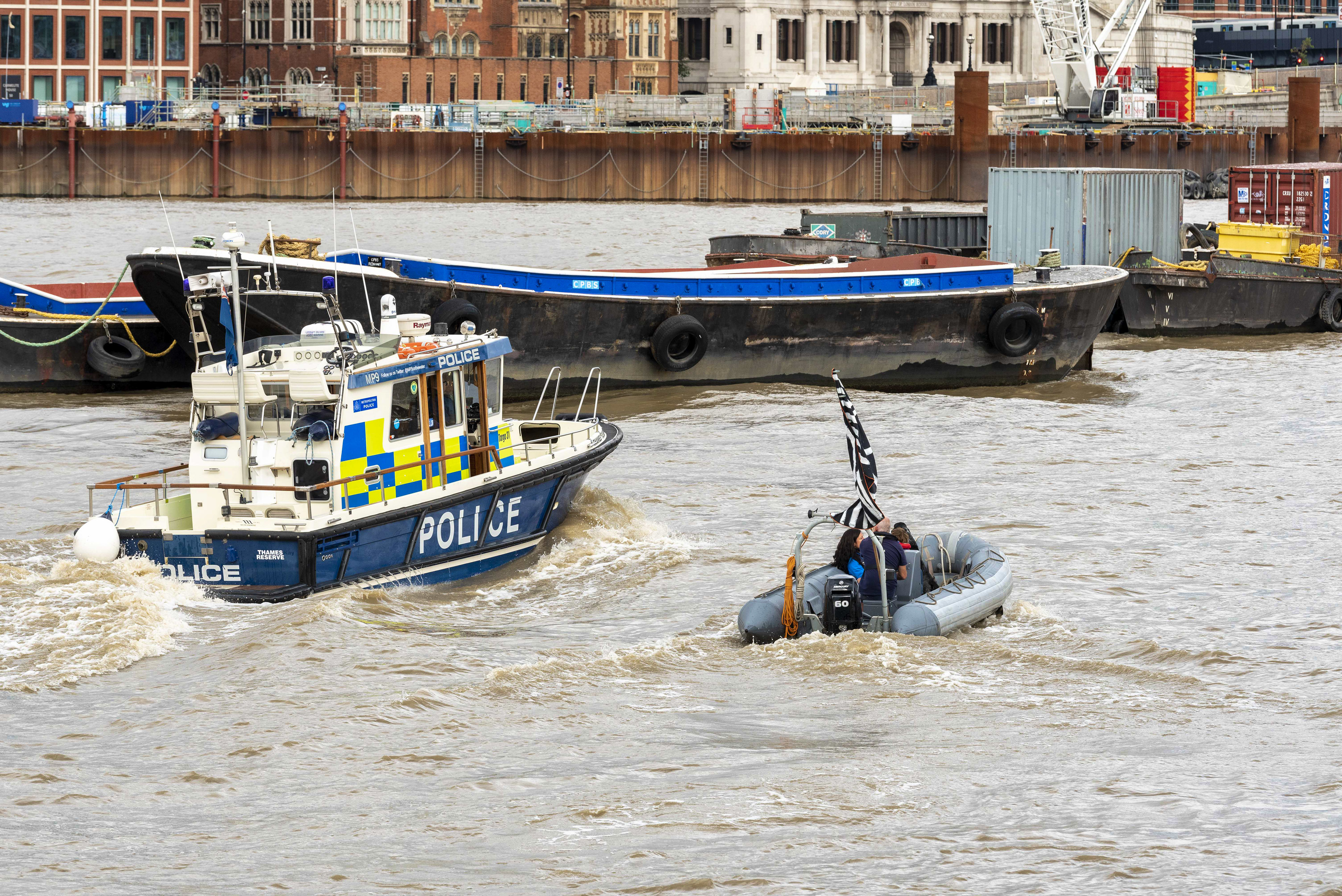 A police launch passes an Extinction Rebellion Marine rib boat on the River Thames during the Extinction Rebellion Macabre Beach Party. A beach party (on grass) next to the River Thames was held by the Extinction Rebellion Marine supporters to highlight the dangers of the extreme weather caused by climate change and sound an alarm for the urgent need to take action now to avert catastrophic flooding in London, the UK and the whole world. (Photo by Dave Rushen / SOPA Images/Sipa USA)