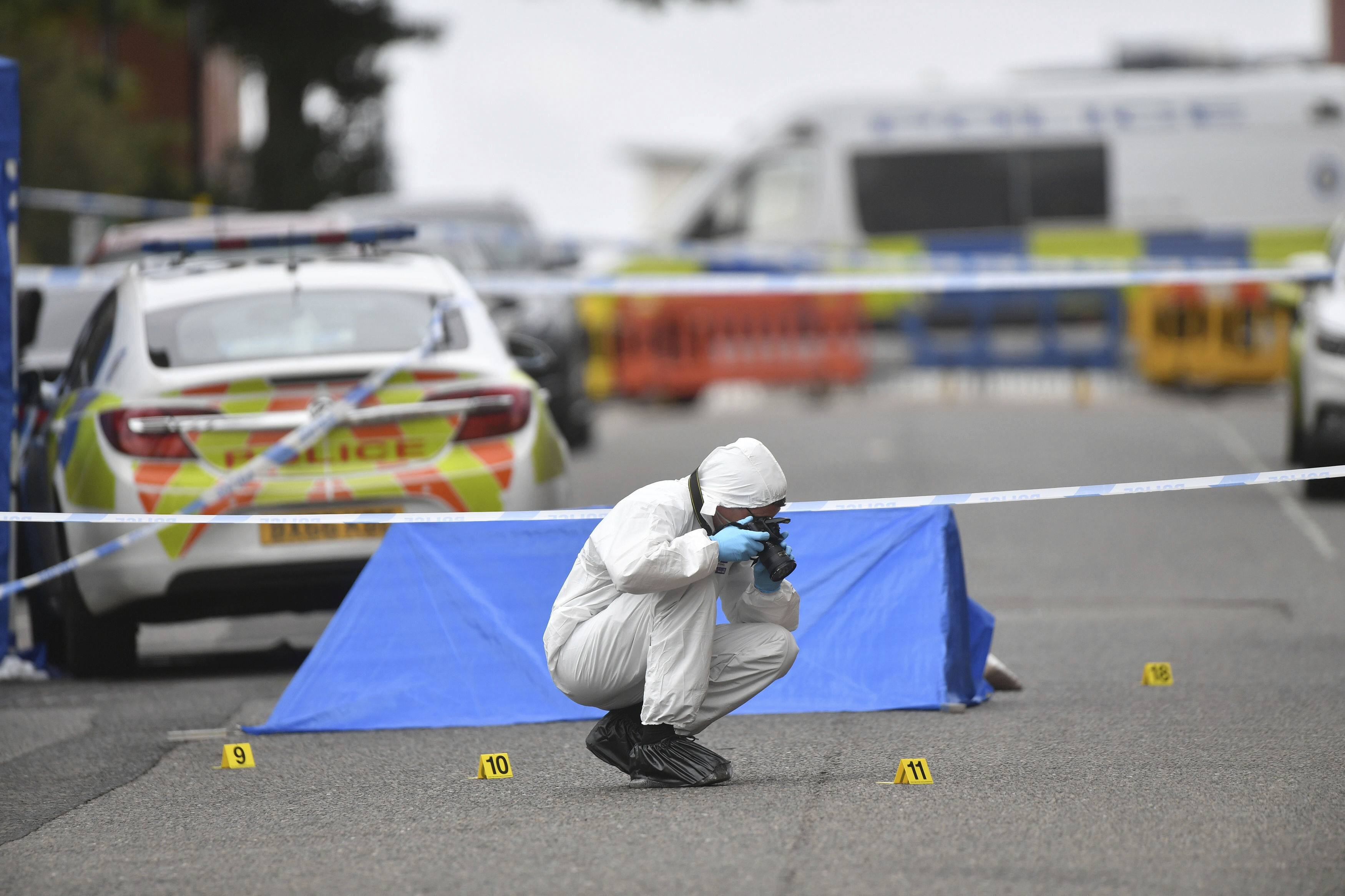 A police forensics officer taking photographs in Irving Street, in Birmingham after a number of people were stabbed in the city centre, Sunday, Sept. 6, 2020. British police say that multiple people have been injured in a series of stabbings in a busy nightlife area of the central England city of Birmingham.(Jacob King/PA via AP)