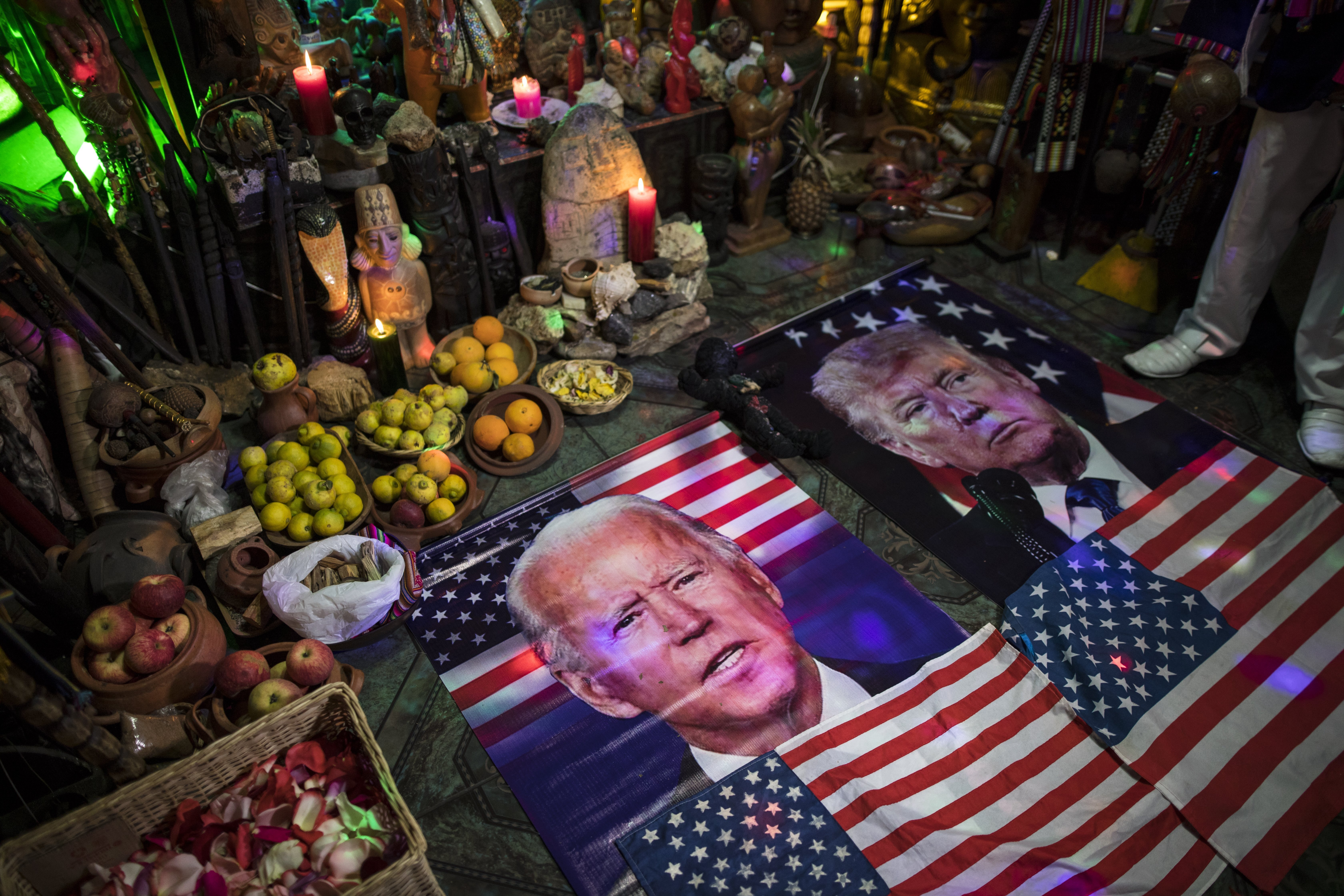 Images of Joe Biden and Donald Trump with American flags are seen next to bowls of fruit and candles