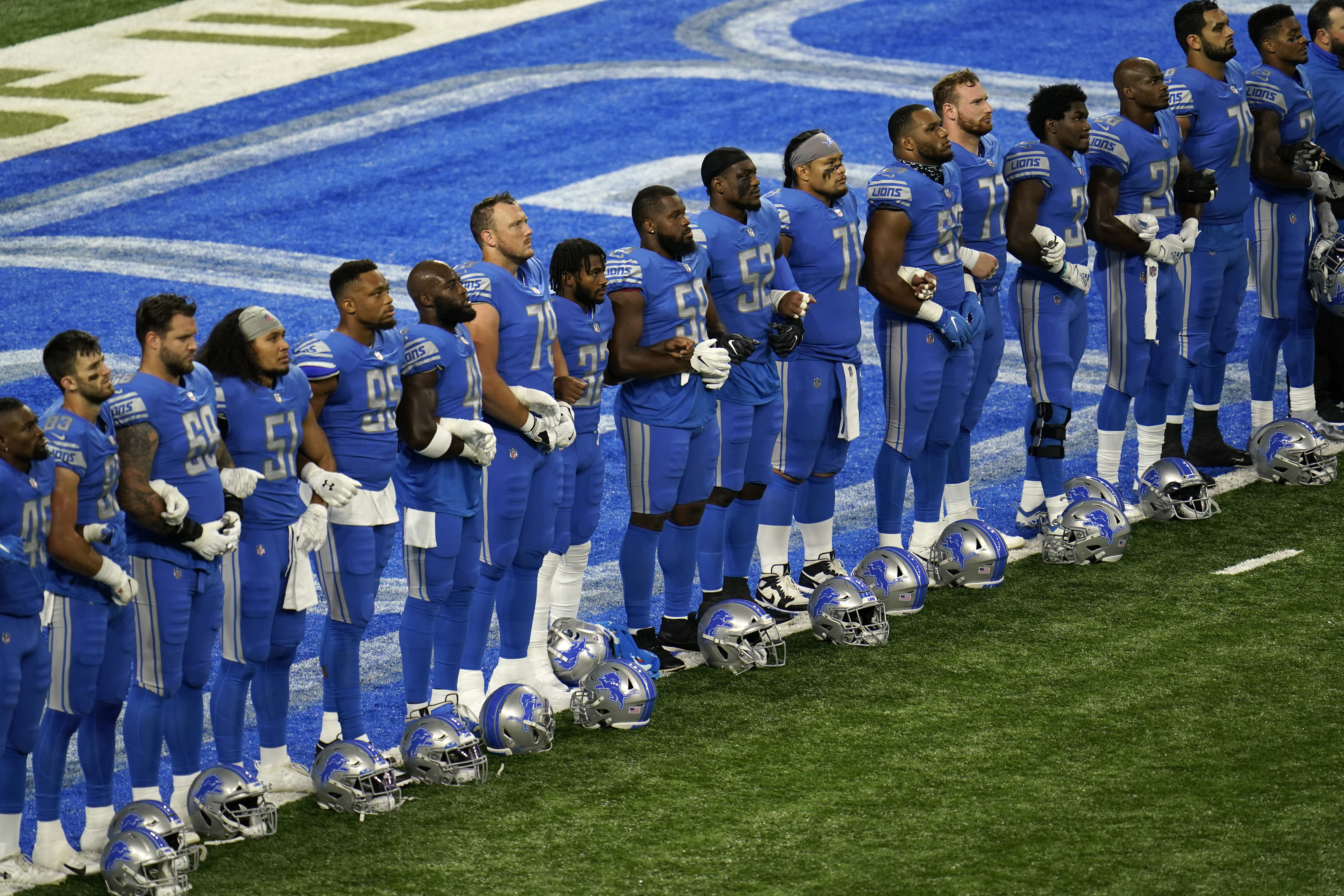 Detroit Lions players stand arm in arm during a social justice video before an NFL football game against the Chicago Bears in Detroit, Sunday, Sept. 13, 2020. (AP Photo/Paul Sancya)