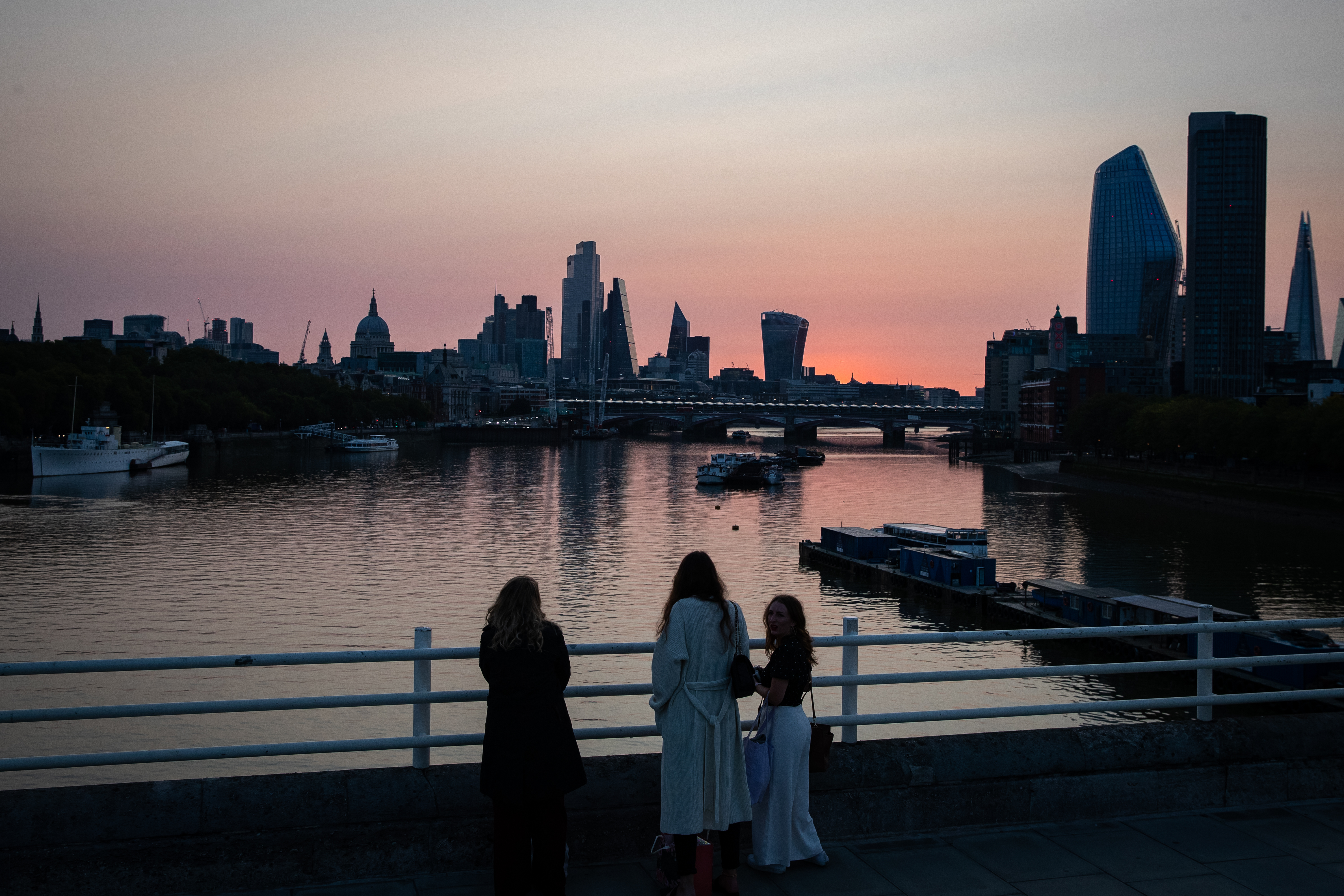The sun rises behind the skyscrapers of the City of London financial district, at the start of a week in which the UK is expected to bask in temperatures of more than 30C. (Photo by Aaron Chown/PA Images via Getty Images)