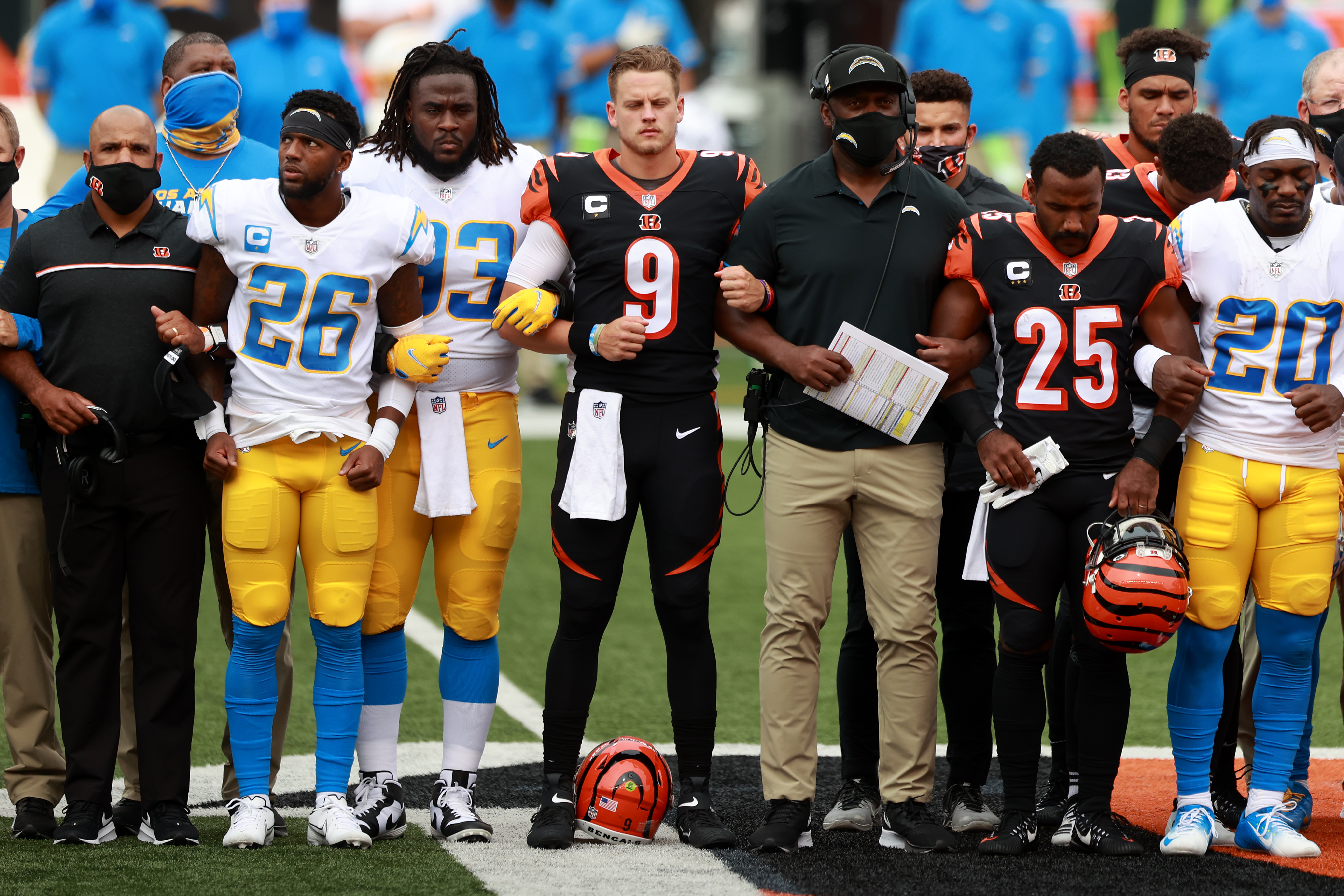 CINCINNATI, OHIO - SEPTEMBER 13: Quarterback Joe Burrow #9 of the Cincinnati Bengals, teammates and the Los Angeles Chargers stand in unity during the U.S. National Anthem at Paul Brown Stadium on September 13, 2020 in Cincinnati, Ohio. The NFL began their 2020 season and the Bengals didn't allow fans in attendance due to the Covid-19 pandemic. (Photo by Bobby Ellis/Getty Images)