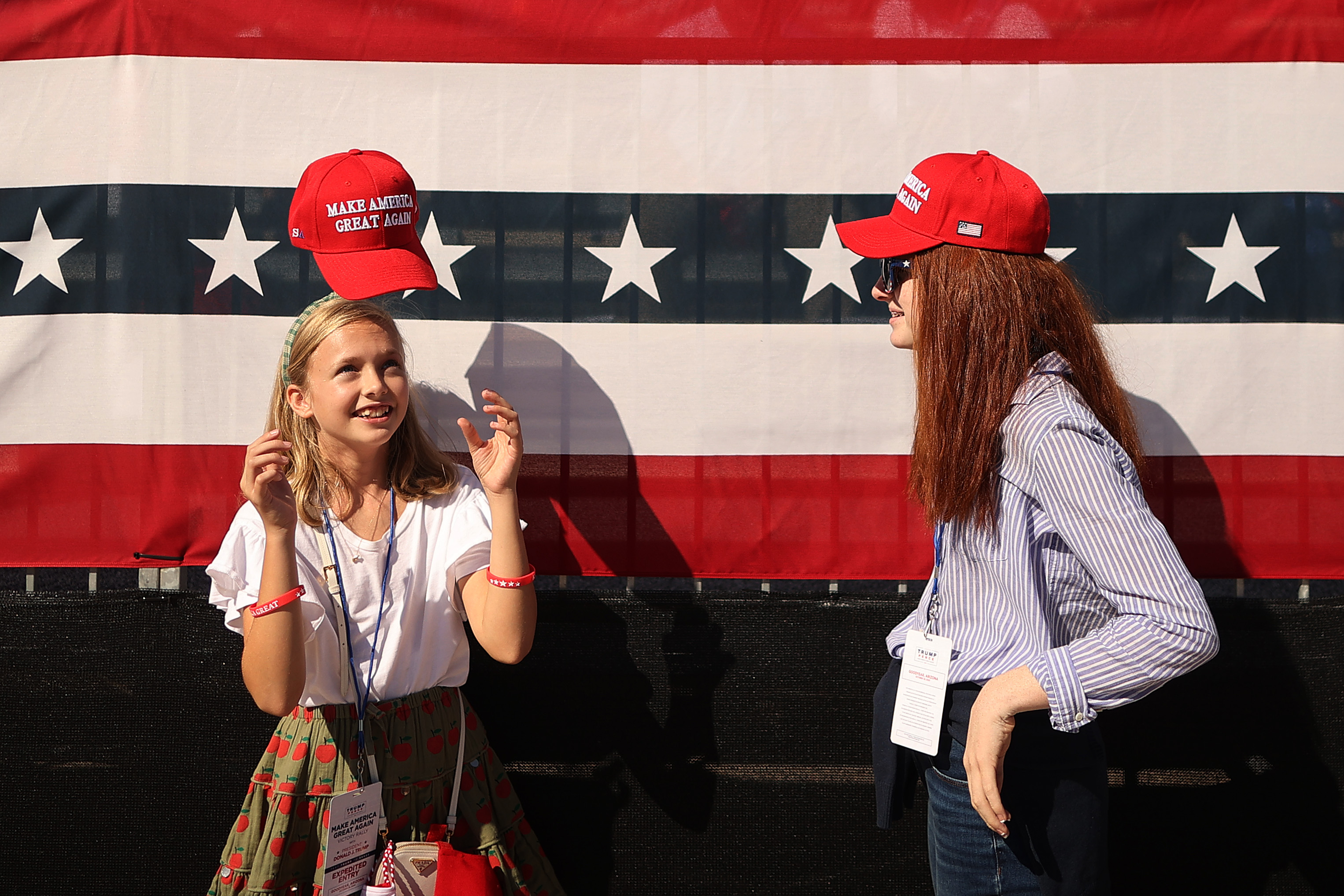 GOODYEAR, ARIZONA - OCTOBER 28: A girl tosses her Make America Great Again hat onto her head while waiting for the start of a campaign rally with U.S. President Donald Trump at Phoenix Goodyear Airport October 28, 2020 in Goodyear, Arizona. With less than a week until Election Day, Trump and his opponent, Democratic presidential nominee Joe Biden, are campaigning across the country. (Photo by Chip Somodevilla/Getty Images)
