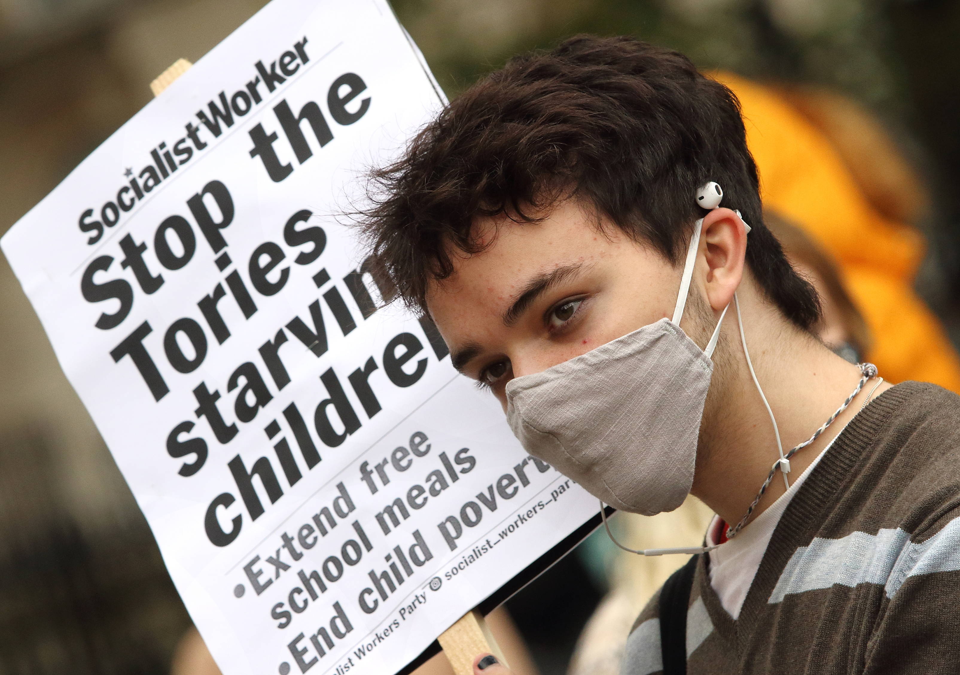 A girl wearing a facemask holds a placard saying 'stop the tories starving children' during the protest. Youth protest outside Downing Street after the UK government MPs voted not to pay for school meals for under privileged children during half term. (Photo by Keith Mayhew / SOPA Images/Sipa USA)