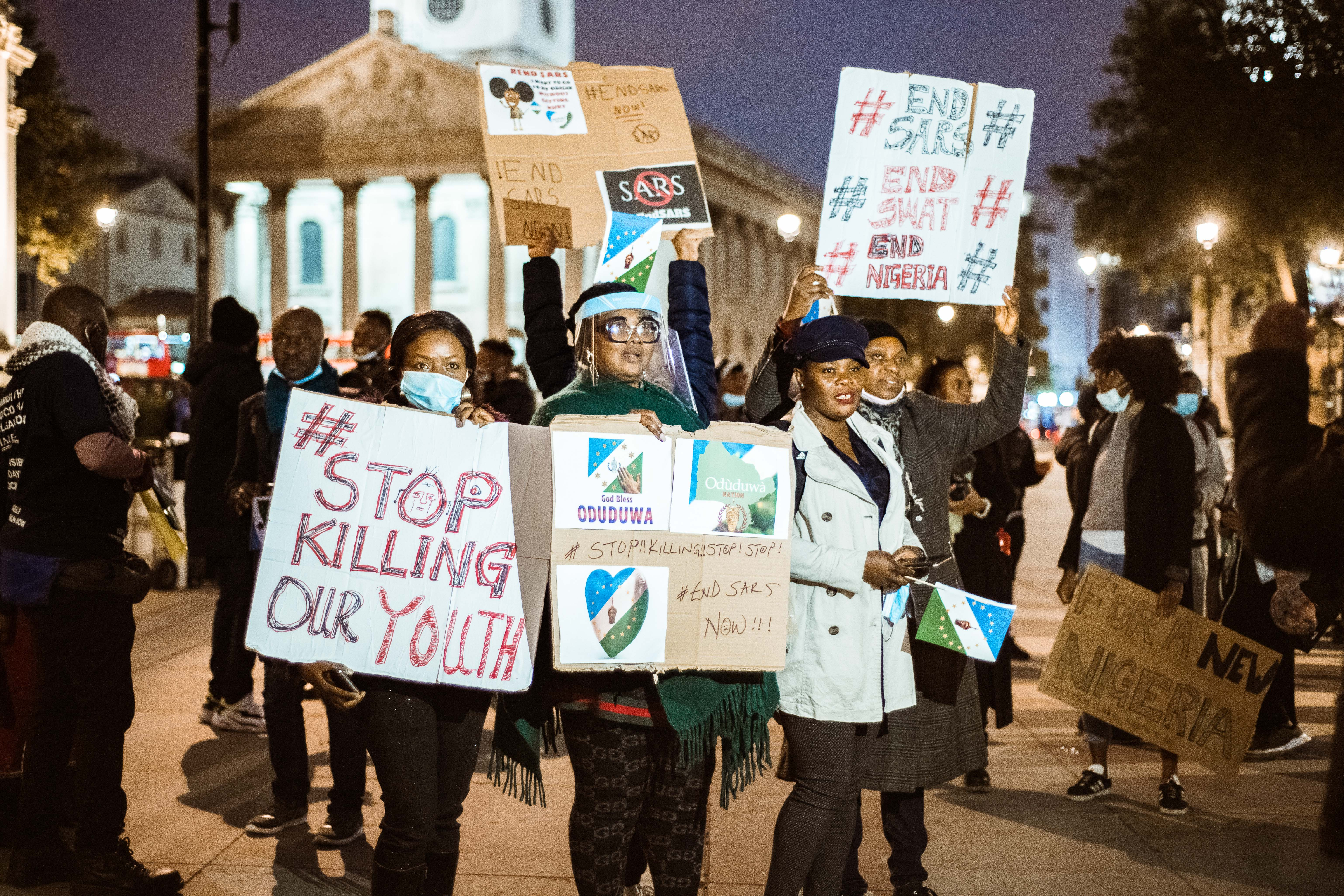 LONDON, ENGLAND - OCTOBER 18:  Demonstrators at the candlelight procession to remember victims of SARS and those assaulted by Nigeria Police gather at Trafalgar Square on October 18, 2020 in London, England. They echo the ongoing #EndSARS protest movement against Nigeria's Special Anti-Robbery Squad, whose officers have been accused of indiscriminate arrests, extortion, and extrajudicial killings. Nigeria's President Muhammadu Buhari recently disbanded the force, replacing it with a new division named SWAT (Special Weapons and Tactics), but the makeover has not placated the protesters.  (Photo by Joseph Okpako/Getty Images)