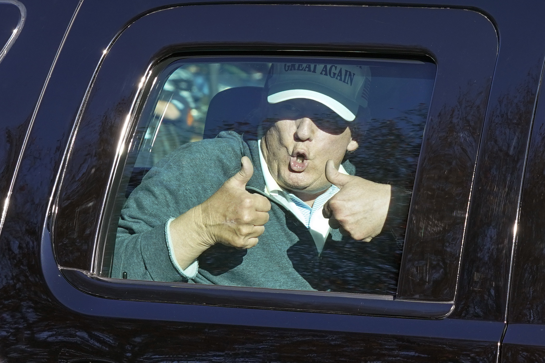 President Donald Trump gives two thumbs up to supporters as he departs after playing golf at the Trump National Golf Club in Sterling Va., Sunday Nov. 8, 2020. (AP Photo/Steve Helber)