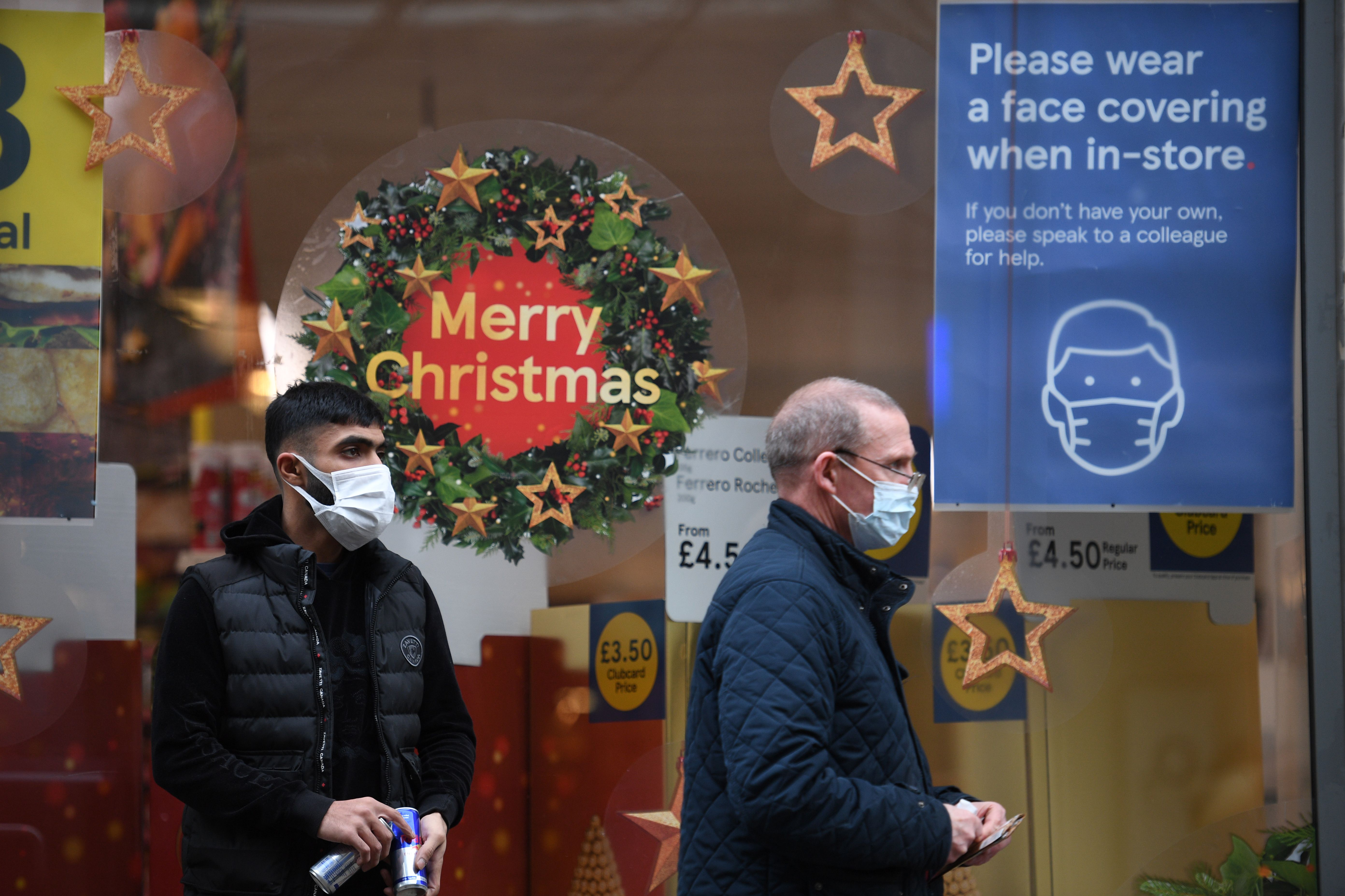 Pedestrians wearing masks because of the novel coronavirus pandemic walk past the window of a closed shop displaying Christmas decoration in the centre of Manchester, northwest England, on November 26, 2020. - London will escape the tightest restrictions once England's national coronavirus lockdown ends next week, the government said Thursday, but major cities including Manchester and Birmingham face at least two more weeks of tough rules. England will return to a regional tiered system when the national regulations end on December 2, with those areas suffering the worst case rates entering the highest Tier 3. (Photo by Oli SCARFF / AFP) (Photo by OLI SCARFF/AFP via Getty Images)