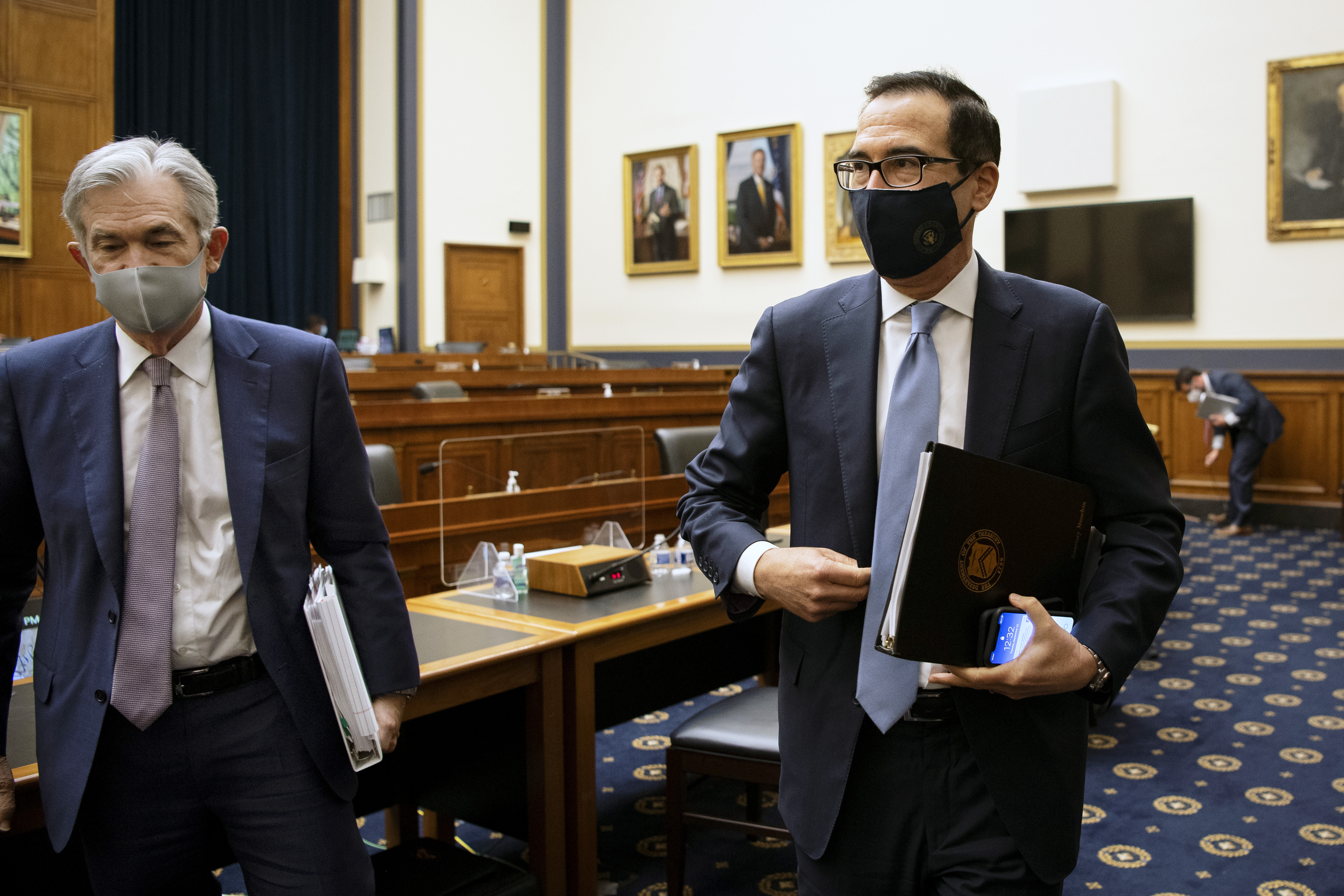 Federal Reserve Chair Jerome Powell, left, and Treasury Secretary Steve Mnuchin leave after a House Financial Services Committee hearing about the government's emergency aid to the economy in response to the coronavirus on Capitol Hill in Washington on Tuesday, Sept. 22, 2020. (Caroline Brehman/Pool via AP)