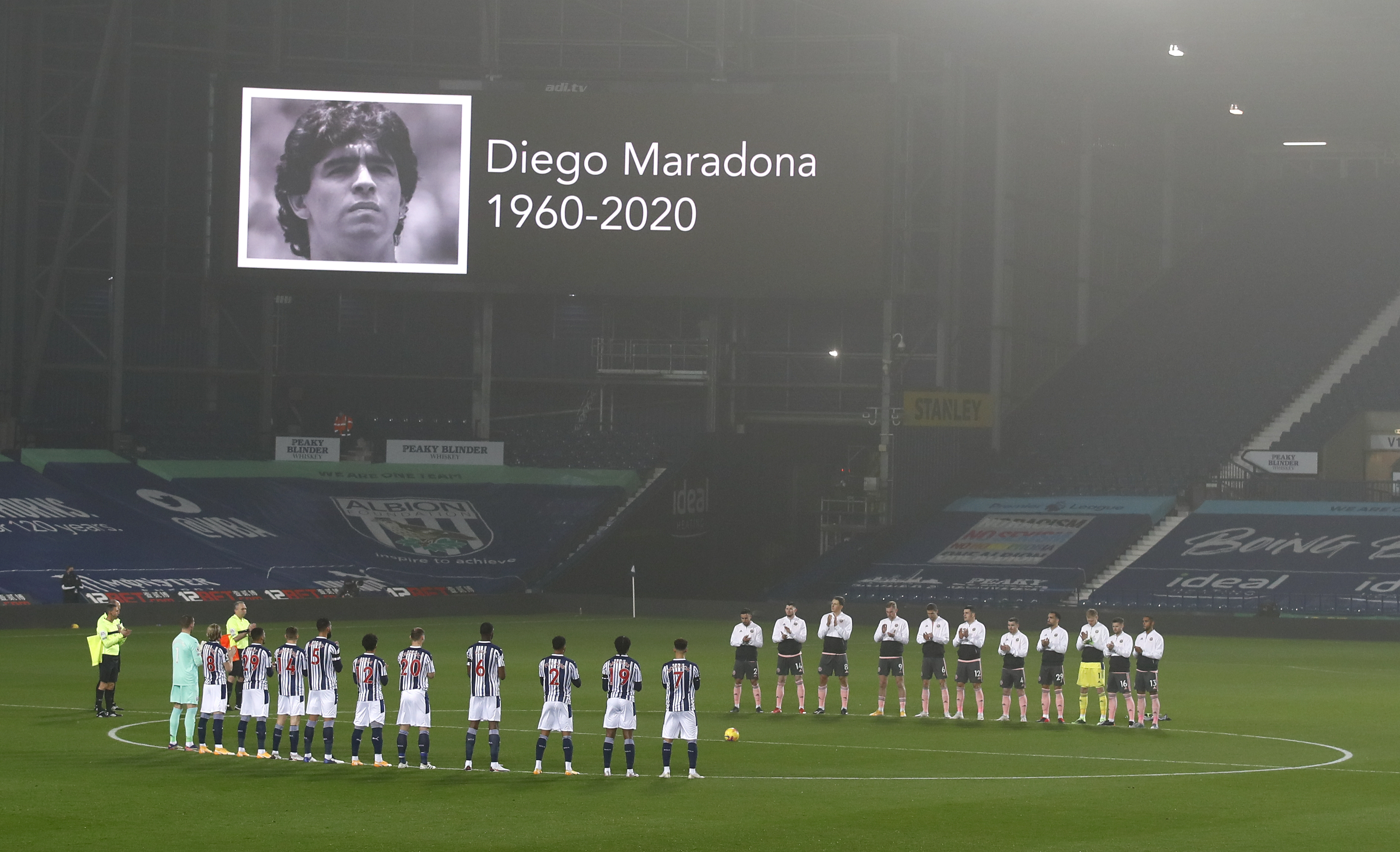 Players stand and applaud for a minute in memory of Argentine soccer star Diego Maradona prior to the start during the English Premier League soccer match between West Bromwich Albion and Sheffield United at The Hawthorns in West Bromwich, England, Saturday, Nov. 28, 2020. (Jason Cairnduff/Pool via AP)