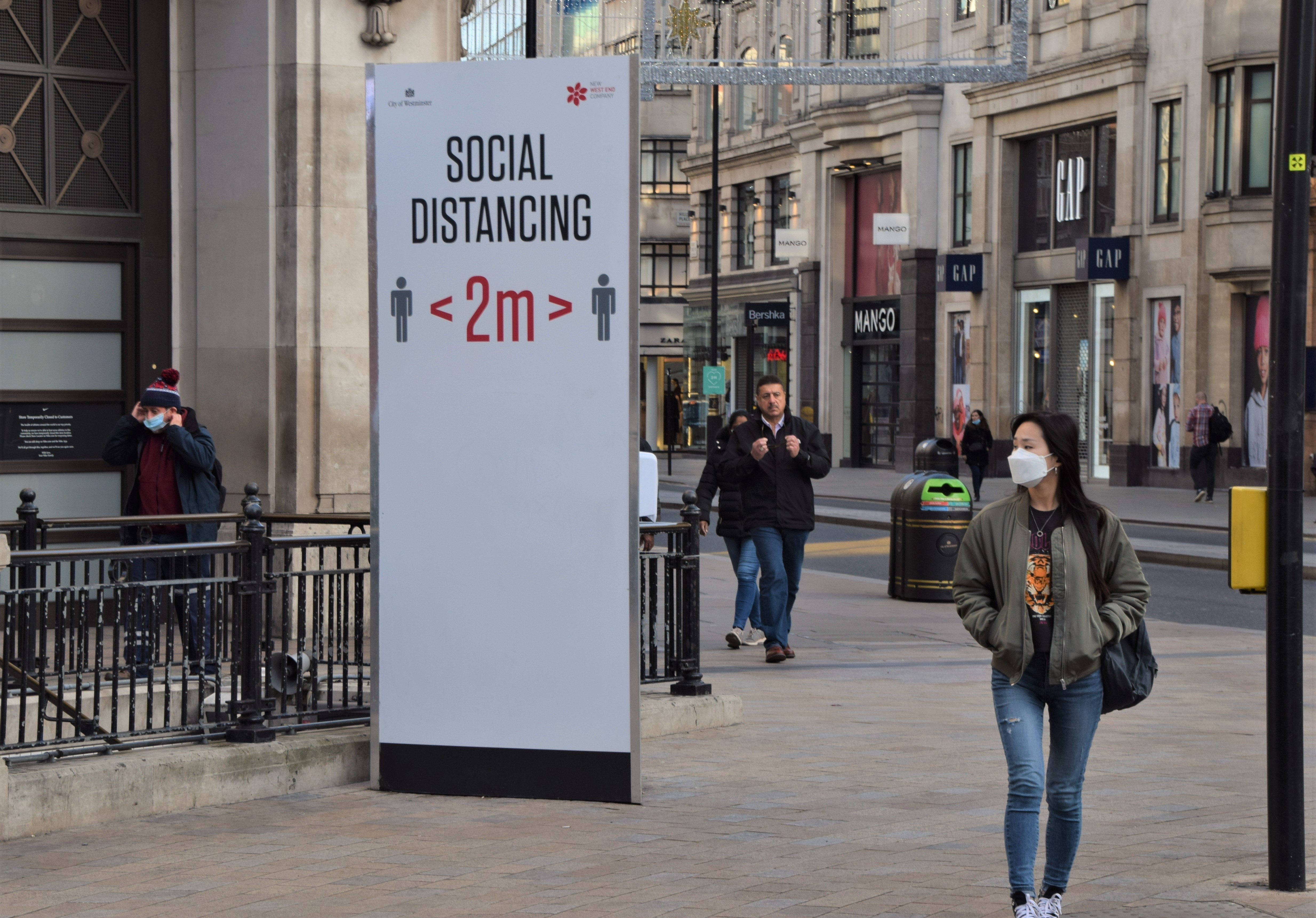 A woman wearing a face mask as a precaution walking past a social distancing sign on Oxford Street. Most shops, restaurants and businesses have closed as the second month-long nationwide Covid 19 lockdown begins in England. (Photo by Vuk Valcic / SOPA Images/Sipa USA)