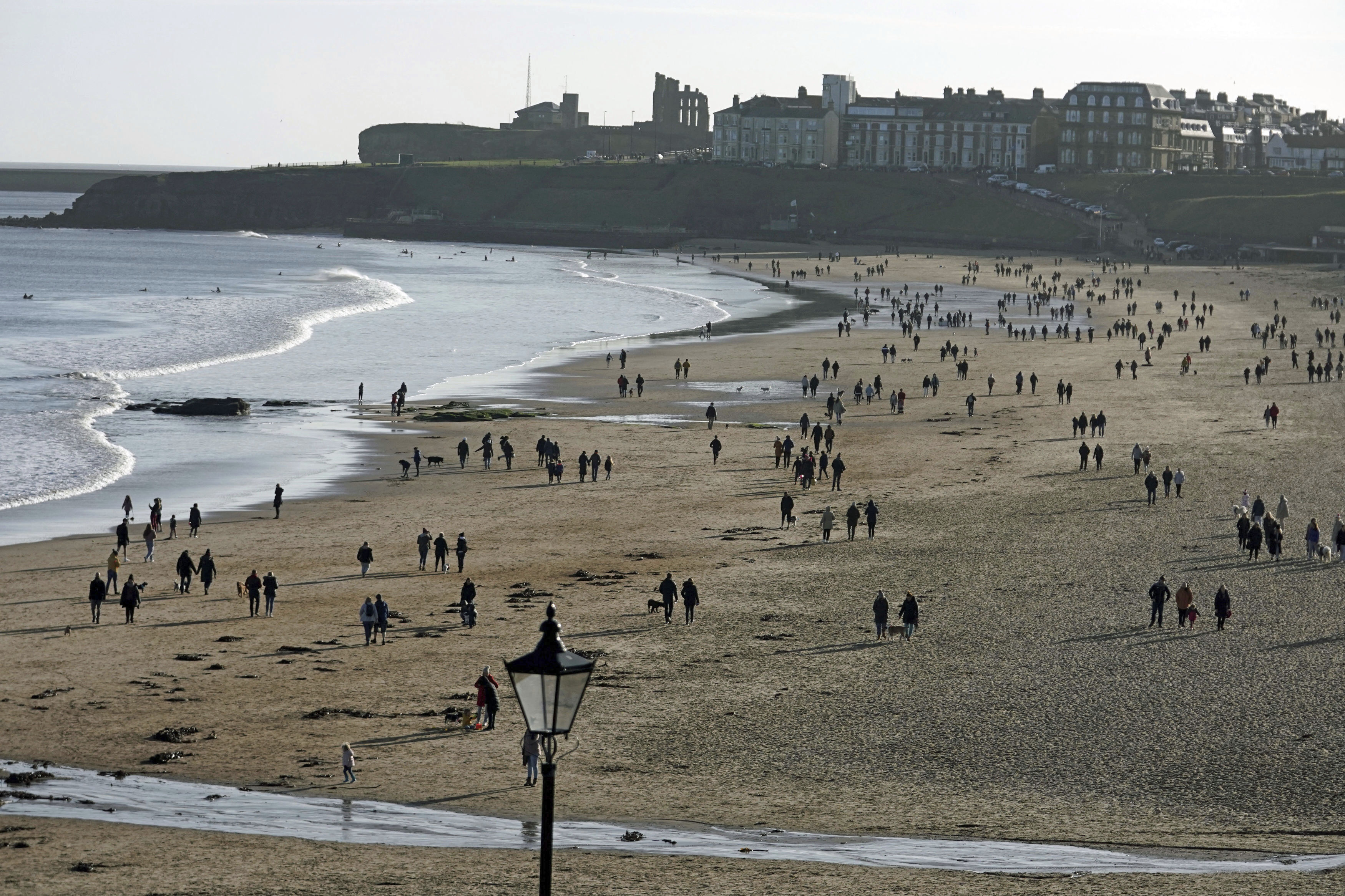 People walking on Tynemouth beach, as England continues a four week national lockdown to curb the spread of coronavirus, in Tyne and Wear, England, Sunday, Nov. 22, 2020. (Owen Humphreys/PA via AP)