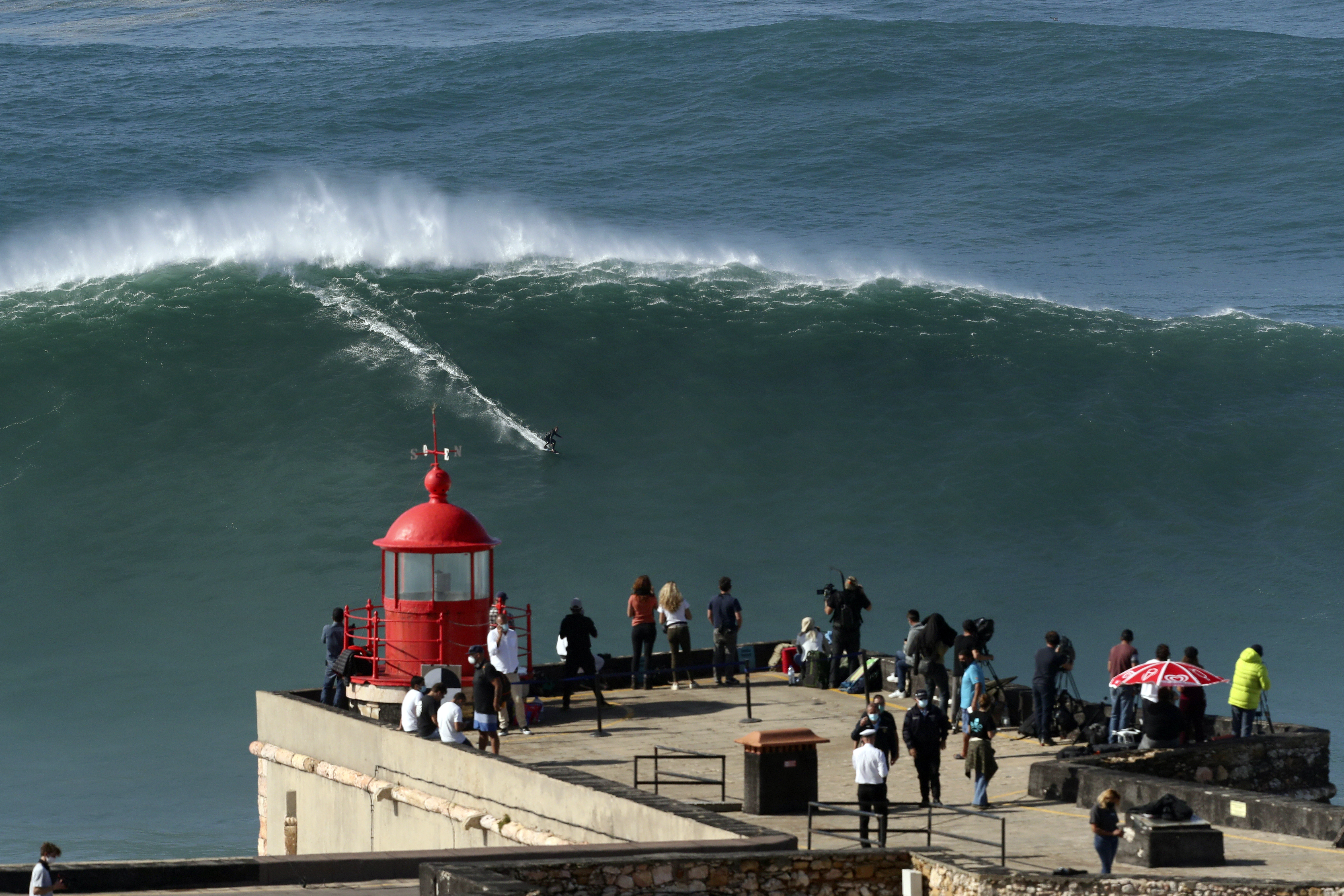 People on the top of the lighthouse watch a surfer ride a wave during a tow surfing session at Praia do Norte or North Beach in Nazare, Portugal, Thursday, Oct. 29, 2020. A big swell generated earlier in the week by Hurricane Epsilon in the North Atlantic, reached the Portuguese west coast drawing big wave surfers to Nazare. (AP Photo/Pedro Rocha)
