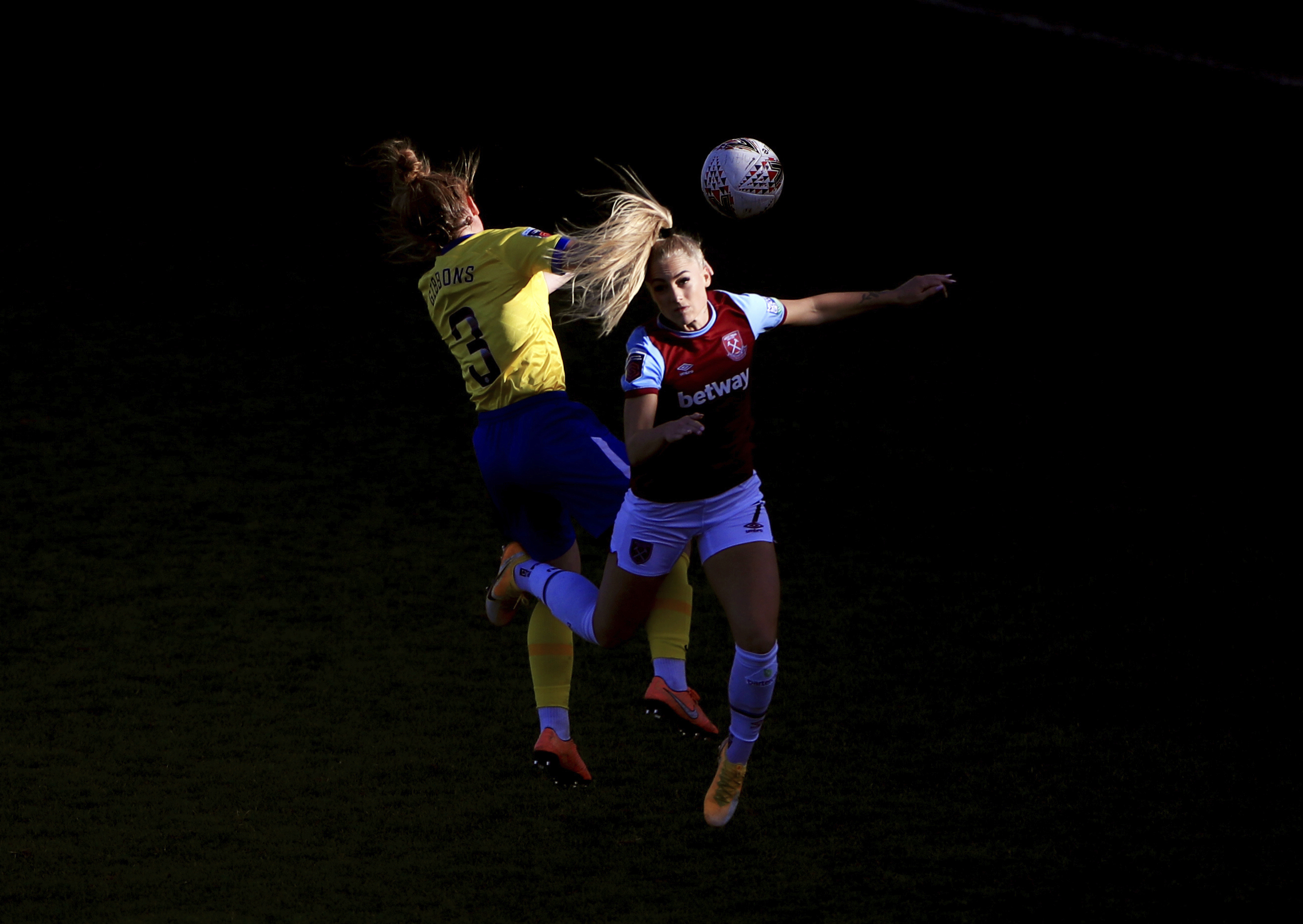 Brighton and Hove Albion's Felicity Gibbons, left, and West Ham United's Alisha Lehmann are caught in sunlight, competing for a header during their Women's Super League soccer match at Chigwell Construction Stadium, in London, Sunday Nov. 15, 2020. (Mike Egerton/PA via AP)
