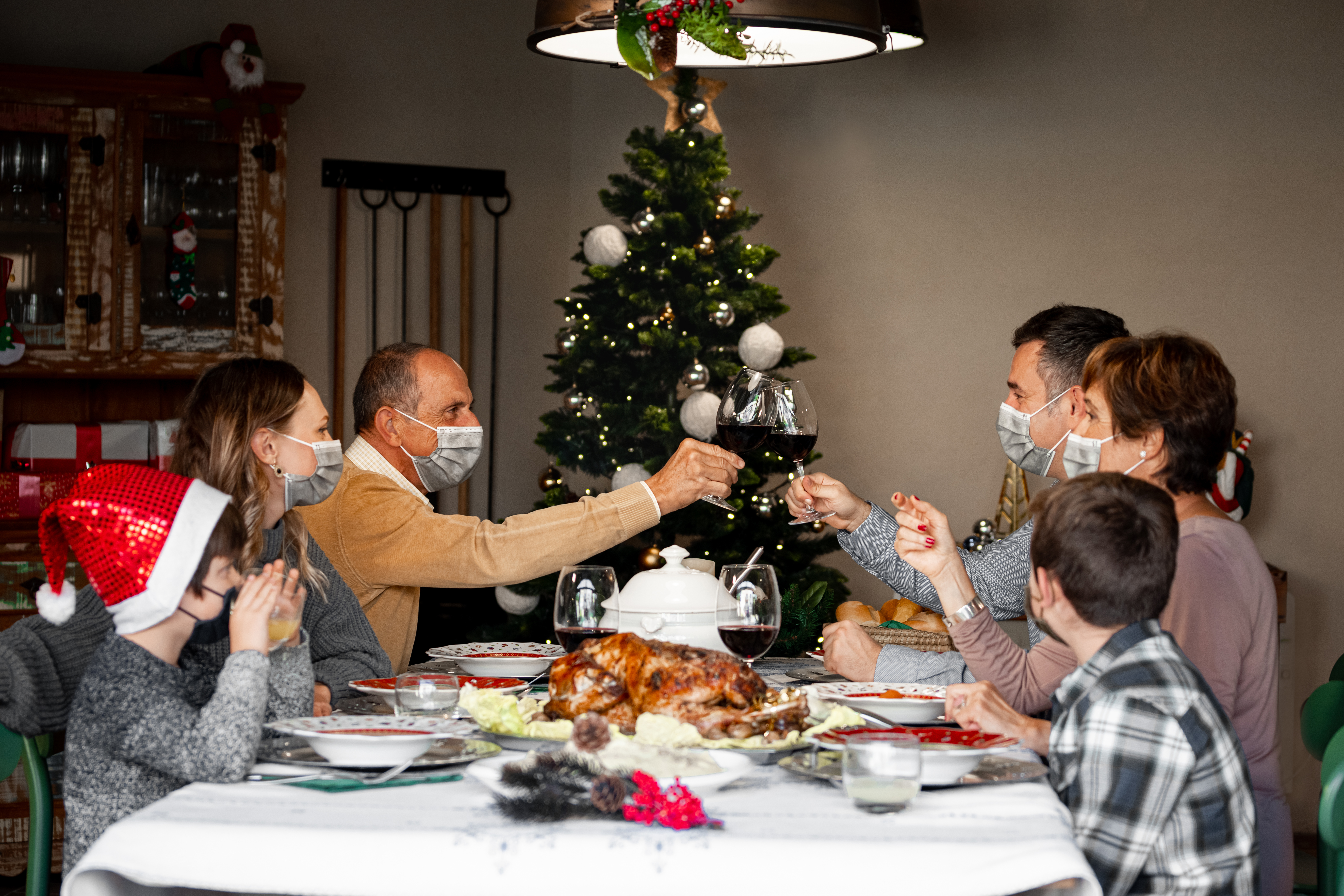 Two family members in surgical masks toast at the Christmas Thanksgiving table at home in the year of the Coronavirus. Happy family members wear surgical masks to comply with new health regulations.