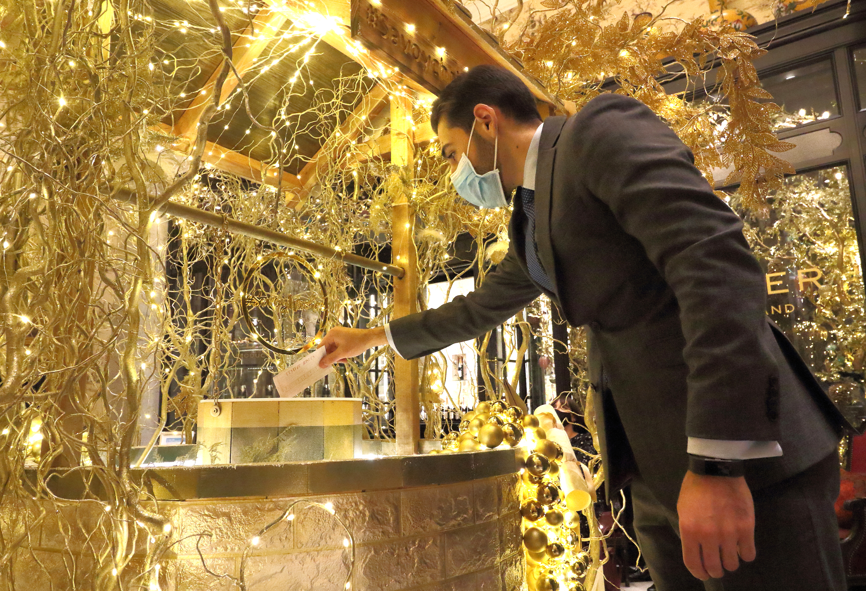 LONDON, UNITED KINGDOM - 2020/12/03: A member of staff wearing a mask posts a wish into the golden wishing well. The Savoy Hotel has reopened and launched a new Christmas charity initiative - Festive Wishes. Launched as the hotel showcases its famous Christmas decorations, The Savoy will grant wishes rewarding kindness and in doing so support two key charities, namely Hospitality Action and The Connection at St Martin in the Fields. (Photo by Keith Mayhew/SOPA Images/LightRocket via Getty Images)