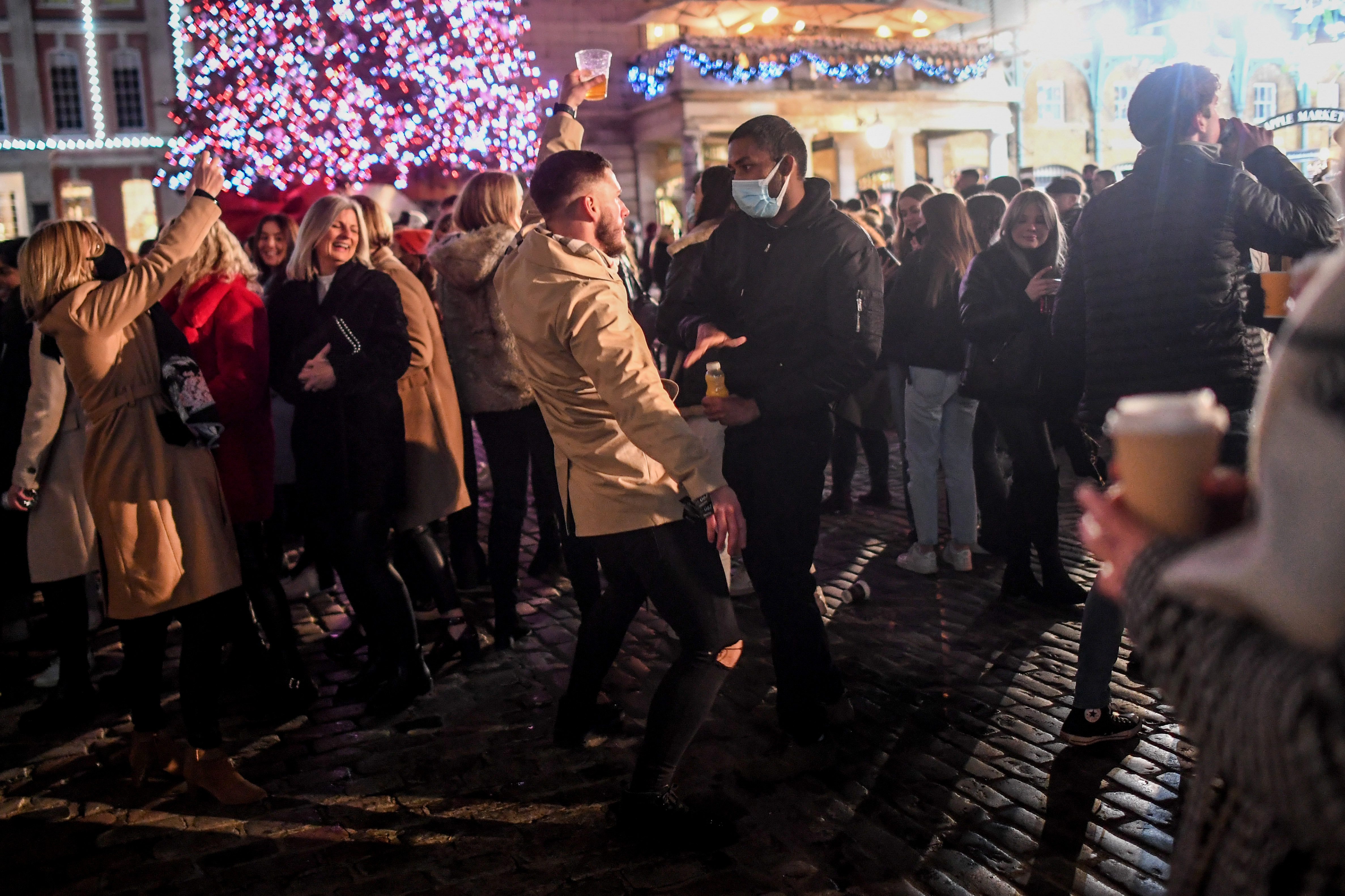 LONDON, ENGLAND  - DECEMBER 05: A man not wearing a mask dances in front of a man wearing a mask in Covent Garden on December 5, 2020 in London, England. On Tuesday night, Dec 1, MPs voted in favour of government proposals to enter England into a tiered system of lockdown beginning at midnight. Residents of Tier Two - High Alert can socialise with anyone they live with or who is in their support bubble in any indoor setting, whether at home or in a public place. Outdoors they must observe the rule of six. Pubs and bars must close, unless operating as restaurants. Hospitality venues can only serve alcohol with substantial meals and must close between 11pm and 5am with last orders called at 10pm. Organised indoor sport, physical activity and exercise classes will be permitted if it is possible for people to avoid mixing with people they do not live with. Schools remain open. (Photo by Peter Summers/Getty Images)