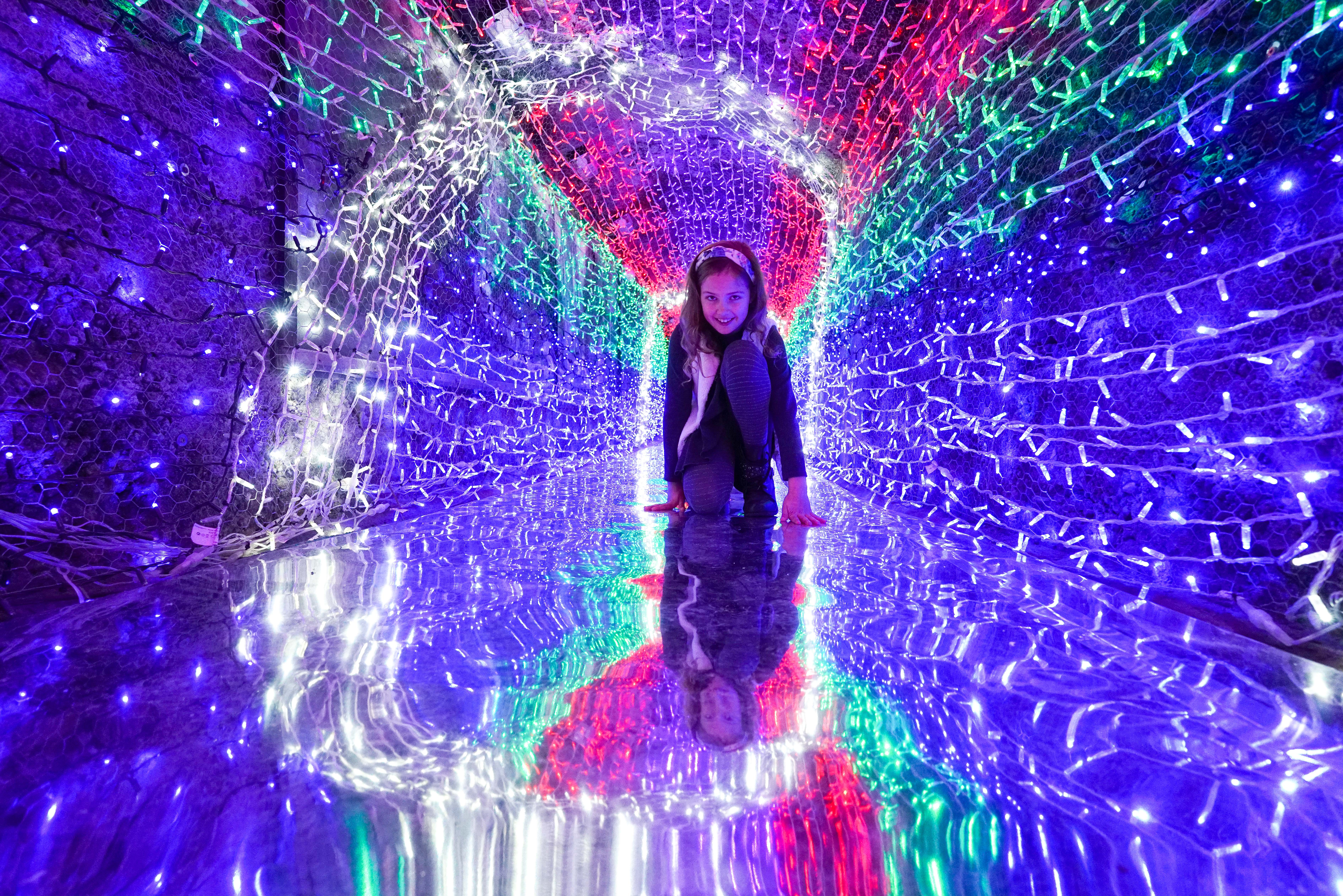 """CHARLESTOWN, ENGLAND - DECEMBER 03: Eight year-old Bellami Smit visits the festive Tunnel of Lights at the Shipwreck Treasure Museum on December 3, 2020 in Charlestown, England. The tunnel is Europe""""u2019s longest underground tunnel of festive lights. (Photo by Hugh Hastings/Getty Images)"""