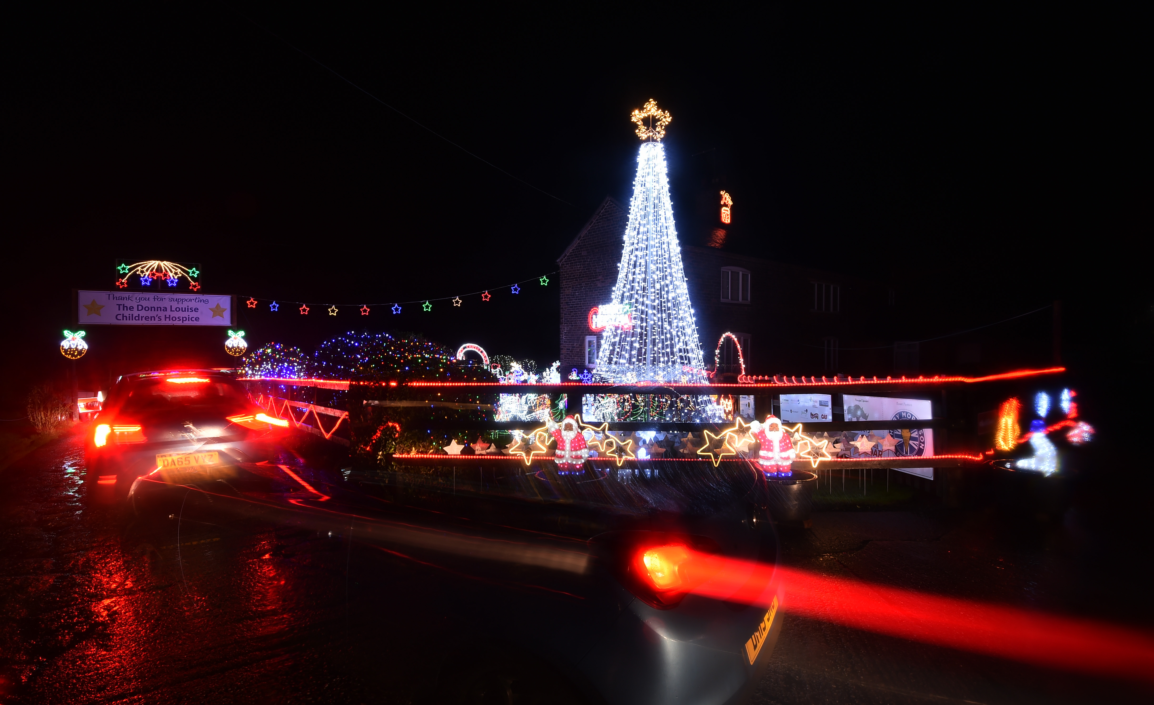 CREWE, ENGLAND - DECEMBER 03: Cars drive past the Weston Christmas light display on December 03, 2020 in Crewe, England. Graham Witter and his family are hosting a drive-through Christmas lights display event at their family home to help raise money for the Donna Louise charity in memory of Graham's sister. (Photo by Nathan Stirk/Getty Images)