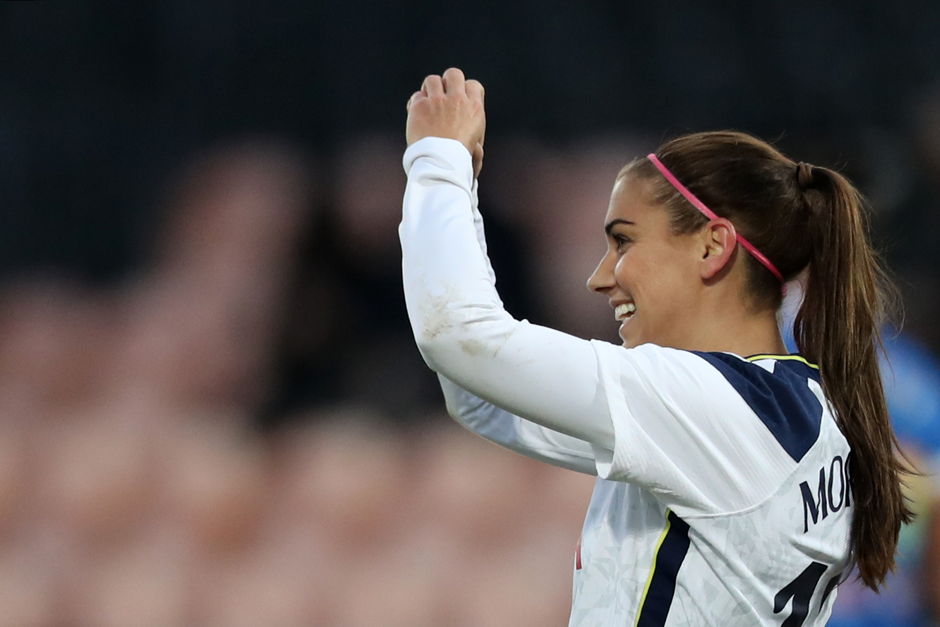 BARNET, ENGLAND - DECEMBER 06: Alex Morgan of Tottenham Hotspur  celebrates after scoring their team's third goal and makes a heart shape with her hands towards her Daughter and Husband in the stands watching the match during the Barclays FA Women's Super League match between Tottenham Hotspur Women and Brighton & Hove Albion Women at The Hive on December 06, 2020 in Barnet, England. A limited number of fans are welcomed back to stadiums to watch elite football across England. This was following easing of restrictions on spectators in tiers one and two areas only. (Photo by Naomi Baker/Getty Images)