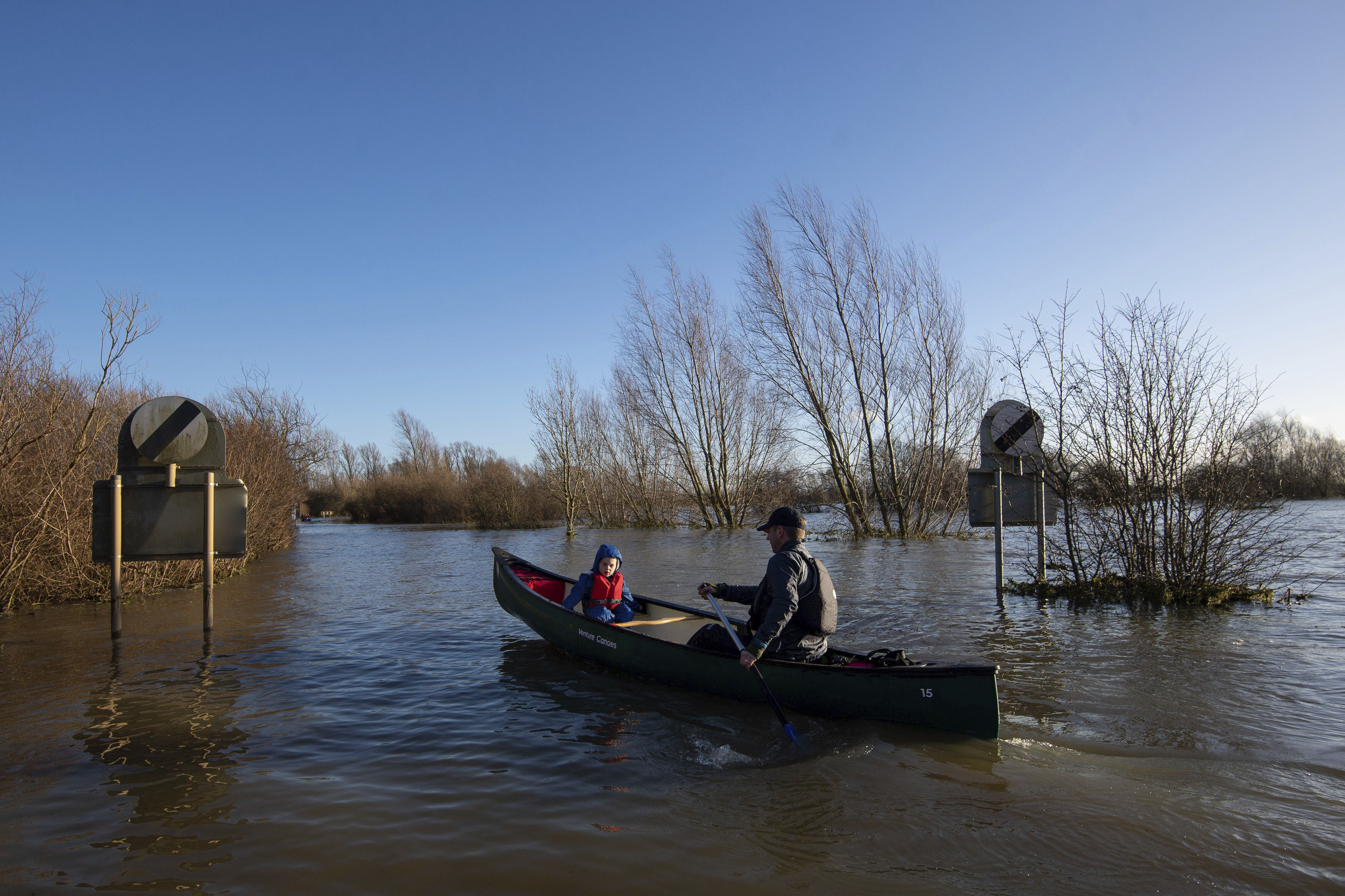 Anthony Gleave and his son Arthur, 3, canoe along the flooded A1101 in Welney, Norfolk, England, Sunday, Dec. 27, 2020. Hurricane-force winds reaching up to 106 miles per hour  (170 kph) and rainstorms battered parts of Britain, disrupting train services and stranding drivers in floodwaters. The Isle of Wight saw Storm Bella's strongest winds at 106mph, while parts of the south coast of England and north Wales also saw gusts of around 80mph (129 kph). (Joe Giddens/PA via AP)