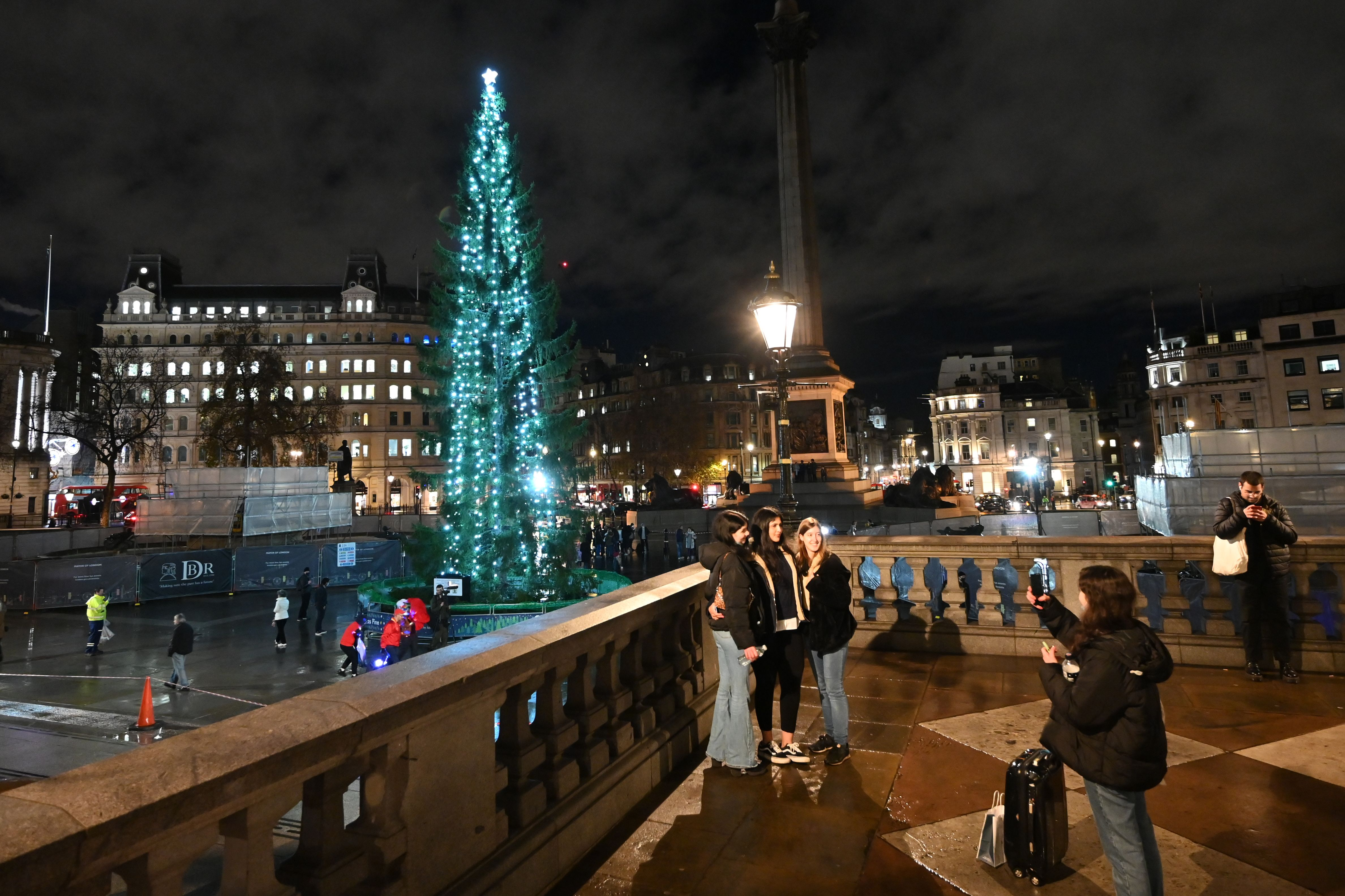 People pose for a photograph in front of the illuminated Christmas tree in Trafalgar Square in central London on December 3, 2020. - The tree is an annual gift to Britain from Norway given as a symbol of friendship and co-operation between the two countries. (Photo by JUSTIN TALLIS / AFP) (Photo by JUSTIN TALLIS/AFP via Getty Images)