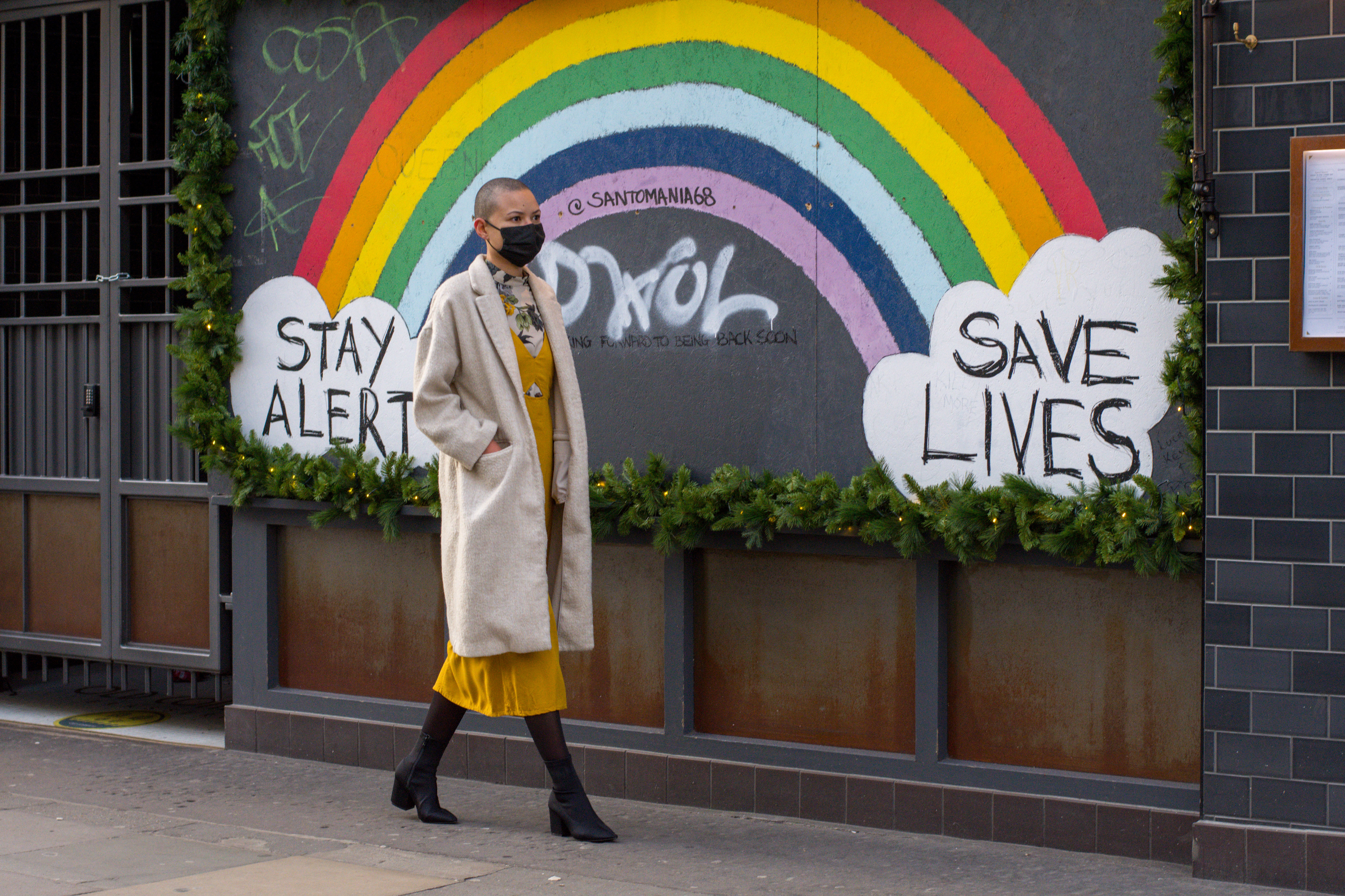 A woman wearing a face mask walks past the Stay Alert Save Lives Rainbow Sign in Soho. As daily Covid19 infection rate hits record high in London, the government is pinning its hopes on the Oxford/AstraZeneca jab. (Photo by Pietro Recchia / SOPA Images/Sipa USA)